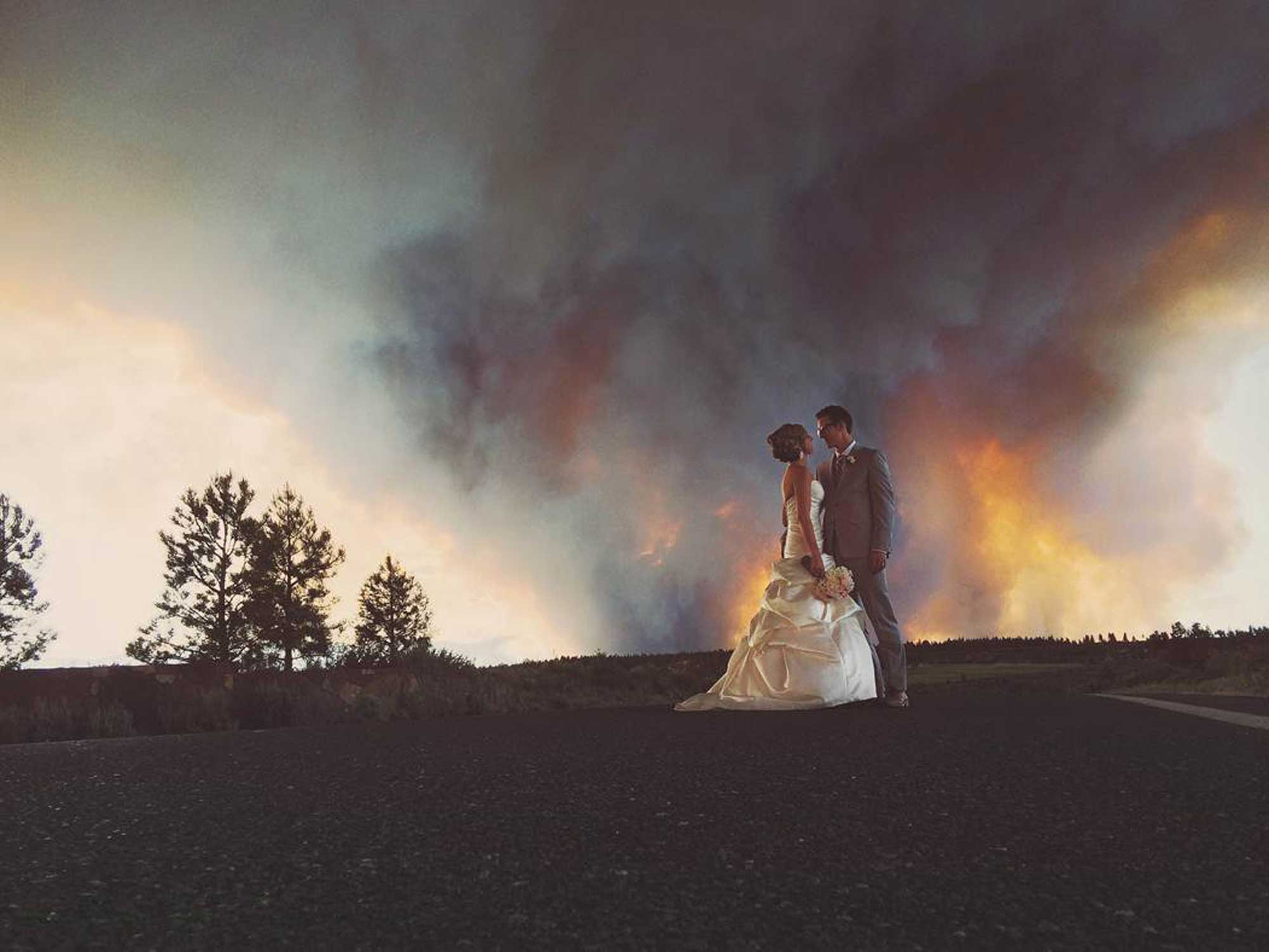Josh Newton, newlyweds Michael Wolber and April Hartley pose for a picture near Bend, Ore. as a wildfire burns in the background, June 7, 2014.