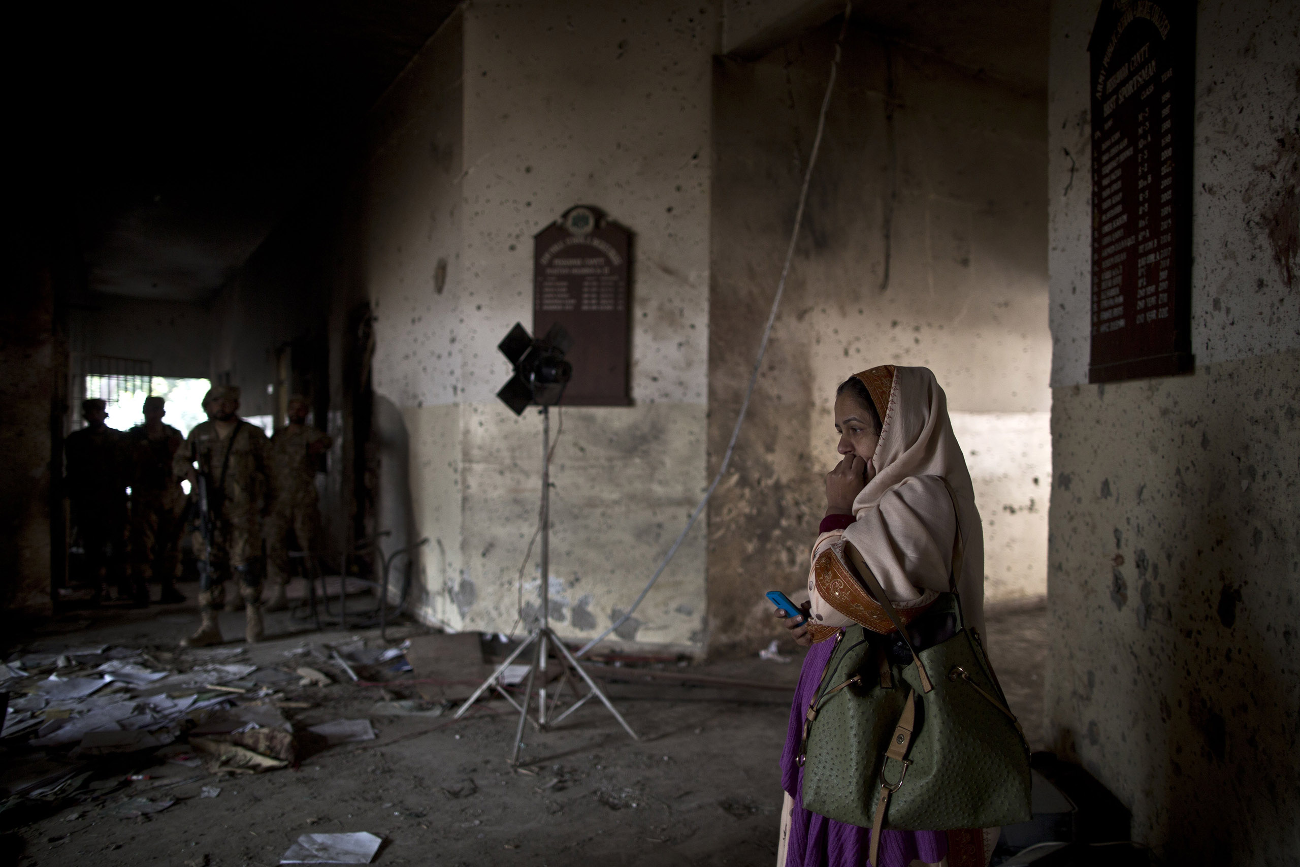 A Pakistani woman looks at the damage inside the Army Public School, which was attacked on Dec. 16 by the Pakistani Taliban. Peshawar, Pakistan. Dec. 18, 2014.