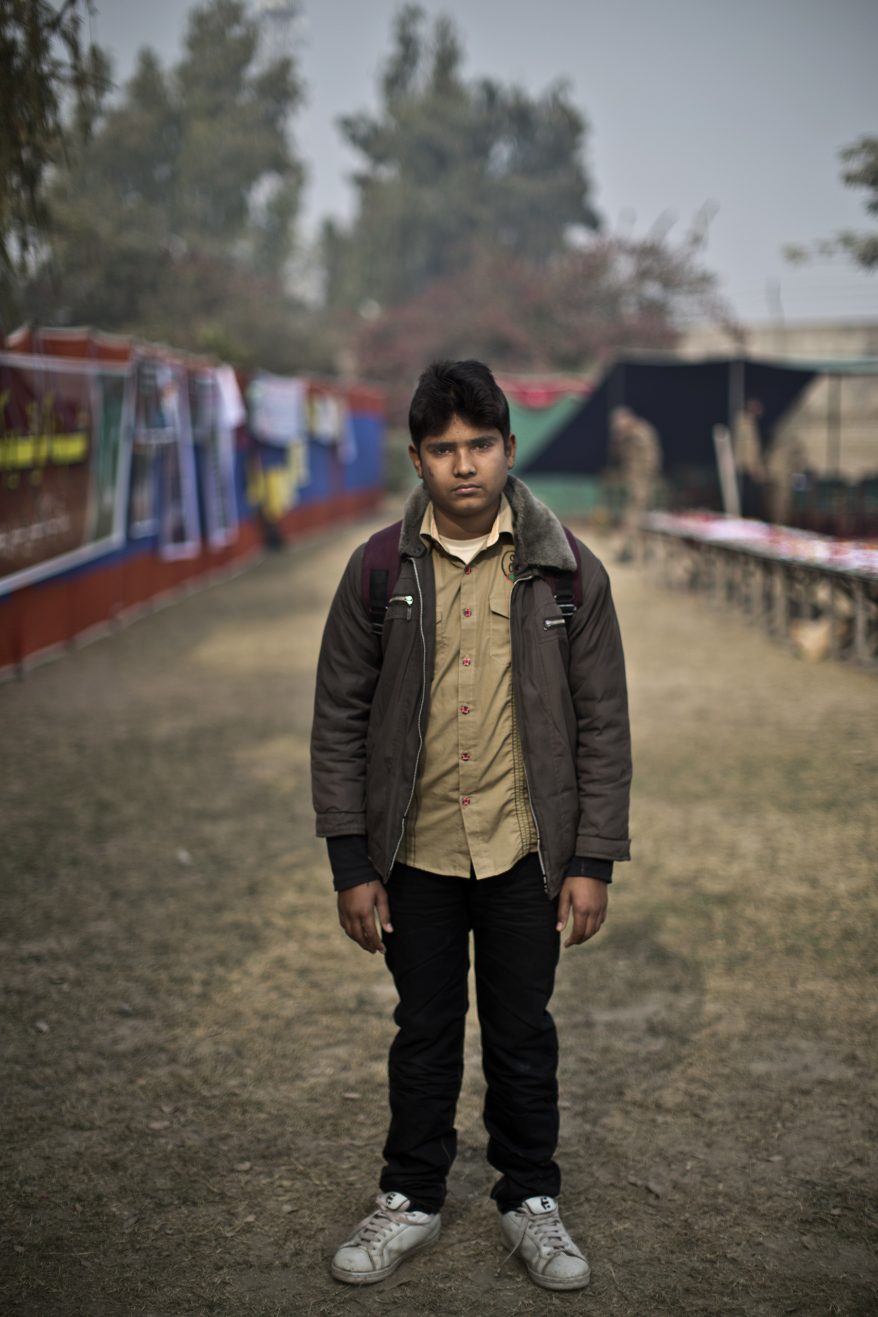 "Entekhab Alam, 14, a student who survived the Pakistani Taliban's attack on the Army Public School on Dec. 16, in the school's yard. Peshawar, Pakistan. Dec. 20, 2014.                                                                      ""Our teacher who gives us the religion class didn't come to the class, so we started playing in the classroom,"" Entekhab said. ""Few minutes after, there was a very loud sound of shooting. I blocked my ears with my hands and ran outside along with a friend, and there was shooting right behind us, and when I reached the gate I noticed that my poor friend got killed. He didn't make it to the gate."""