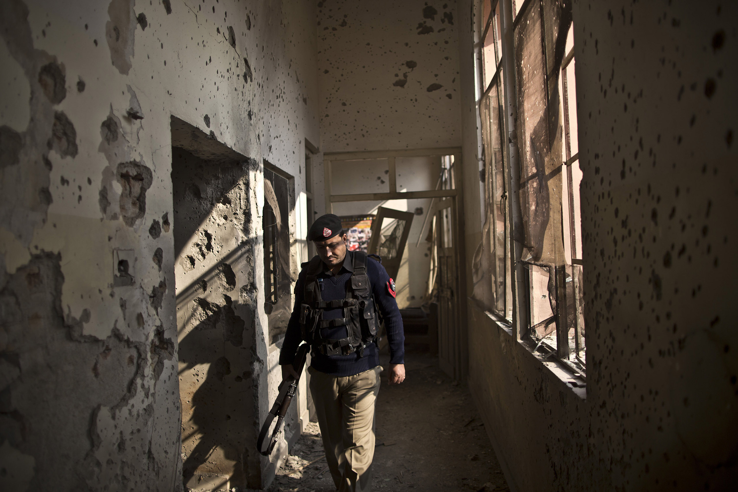 A Pakistani police officer walks through a hallway inside the Army Public School, which was attacked on Dec. 16 by the Pakistani Taliban. Peshawar, Pakistan. Dec. 18, 2014.