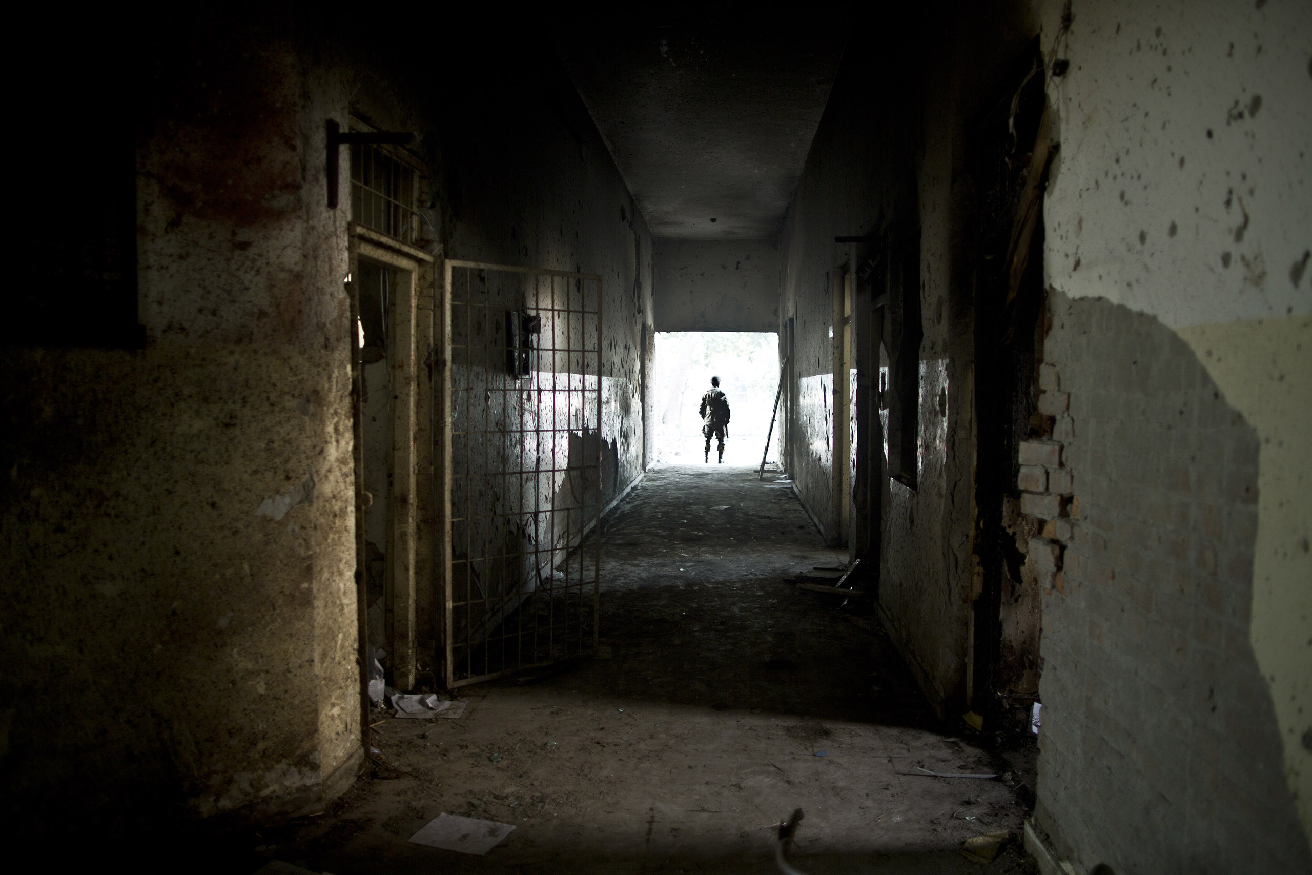 A man stands at the exit of  a hallway that was heavily damaged in the Pakistani Taliban's Dec. 16 attack on the Army Public School. Peshawar, Pakistan. Dec. 18, 2014.