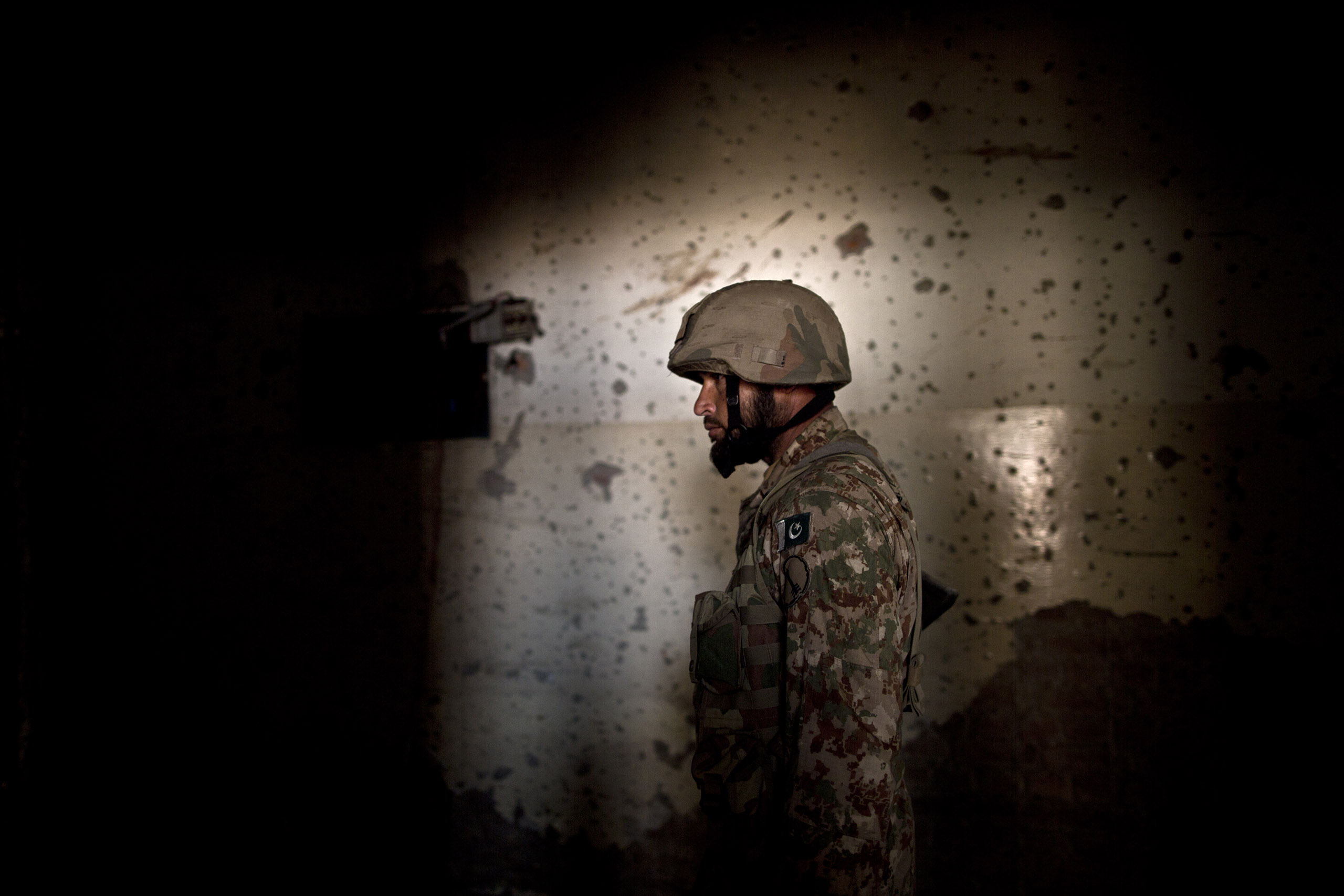 A Pakistani army officer stands in front of a bullet-riddled wall inside the Army Public School, which was attacked on Dec. 16 by the Pakistani Taliban. Peshawar, Pakistan. Dec. 18, 2014.