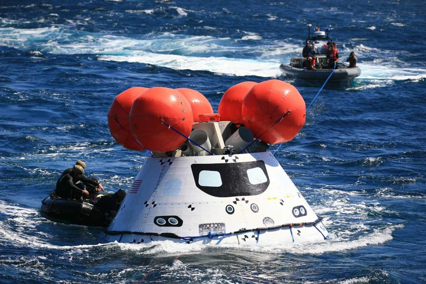 Team members work to secure a test version of Orion in the Pacific Ocean during a test recovery mission.