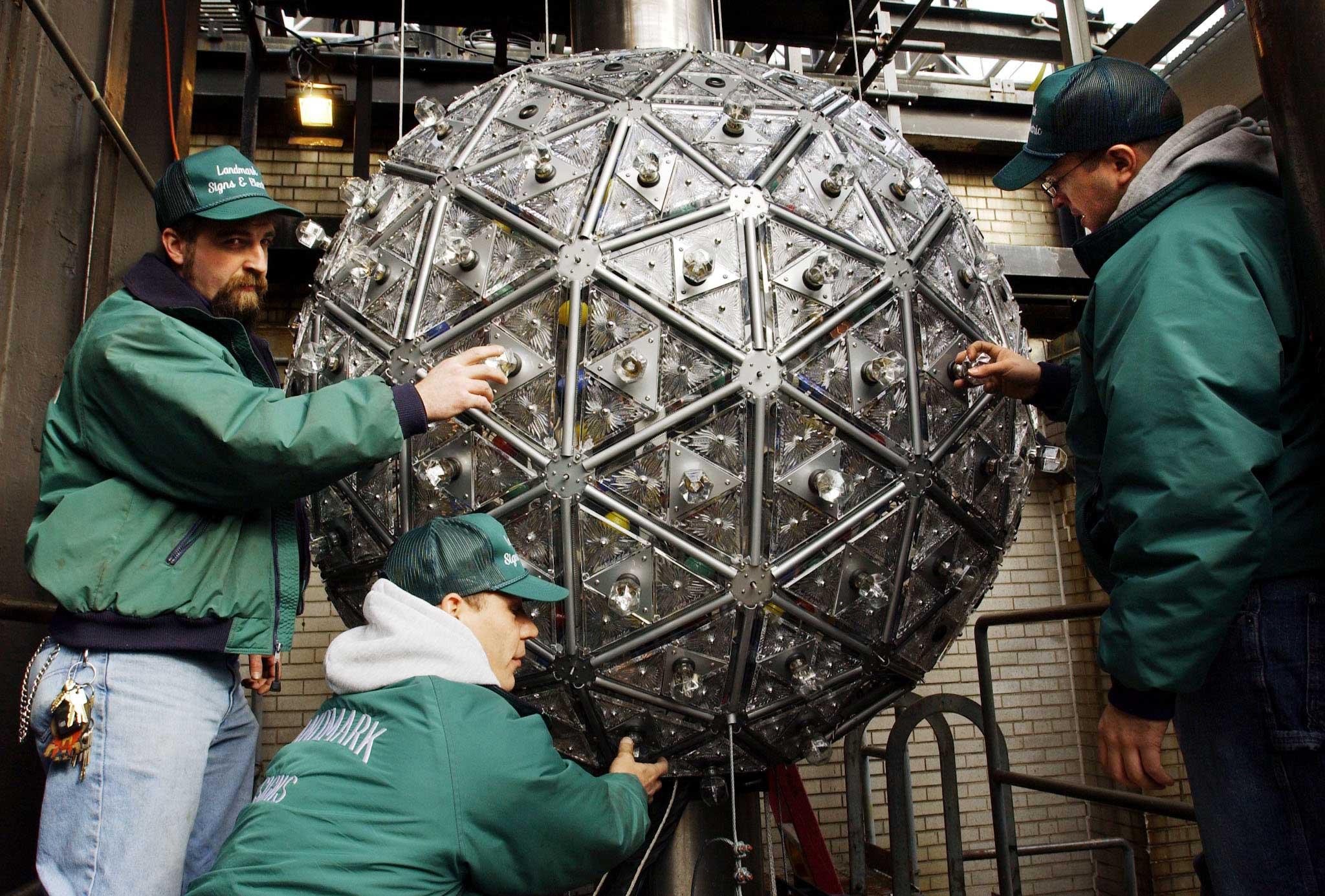Peter Gravagna (L), Raymond Nieves (C) and Felix Ortega (R), of Landmark Signs, install light bulbs on the New Year's Eve Ball in New York City on Dec. 28, 2001.