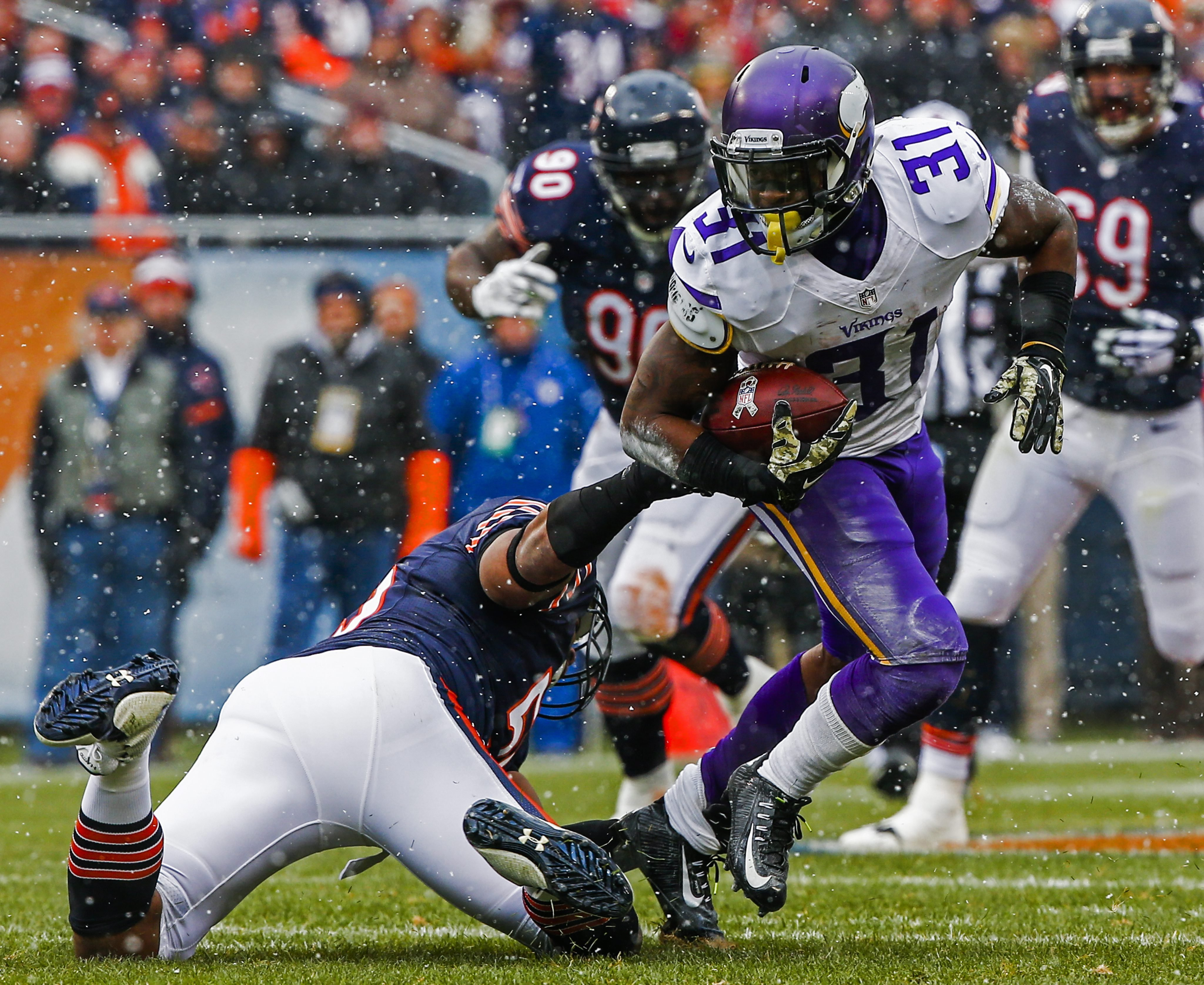 Minnesota Vikings offensive player Jerick McKinnon breaks away from Chicago Bears defensive player Lance Briggs as snow falls in the first half of their game at Soldier Field in Chicago on Nov. 16, 2014.