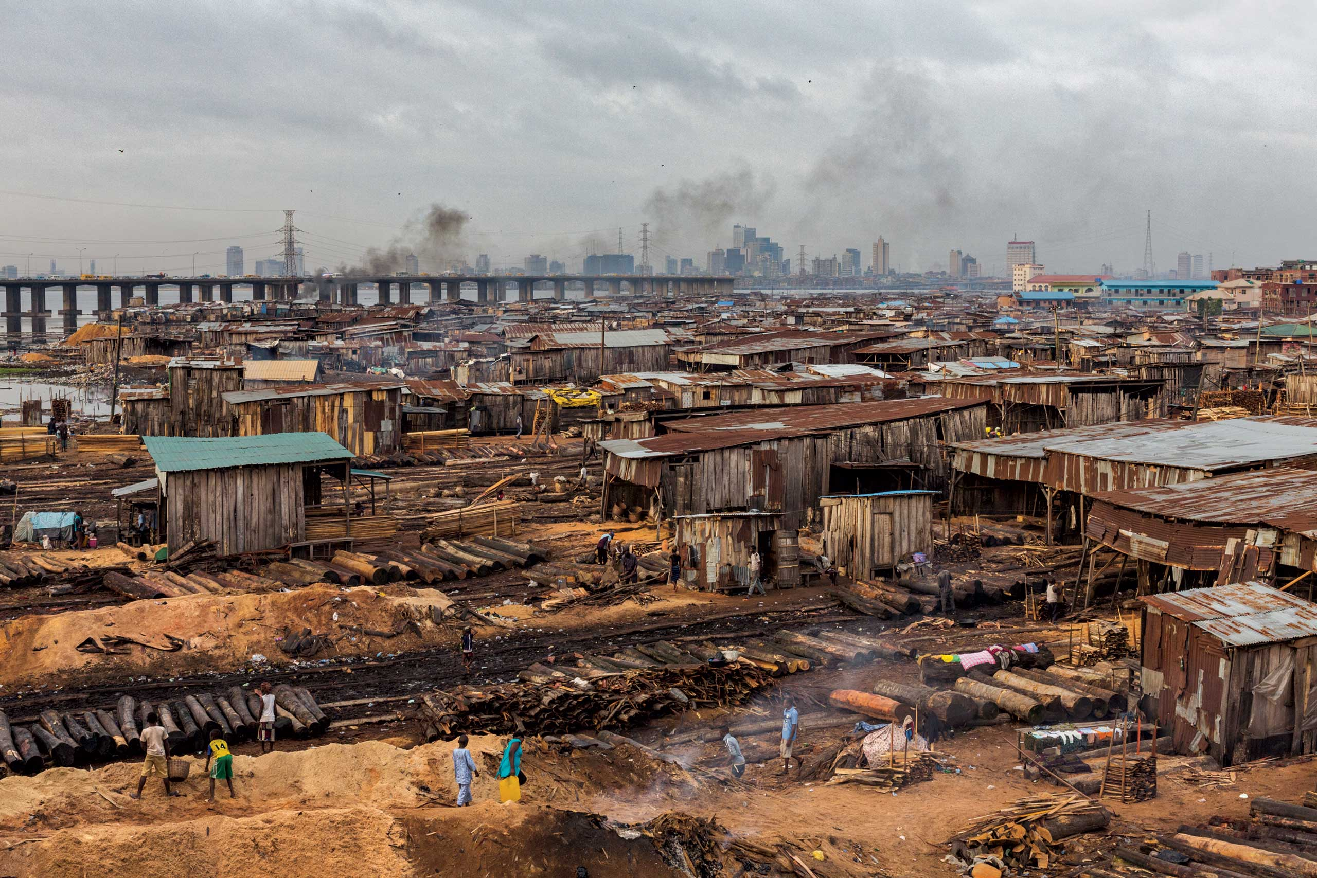 From the January issue of National Geographic magazine: Africa's First CityThousands live and work in the sawmill district on mainland Lagos, a patchwork of workshops and shanties that twice in recent years has been devastated by fires. The towers where Nigeria's wealth is made loom across Lagos Lagoon behind the Third Mainland Bridge.