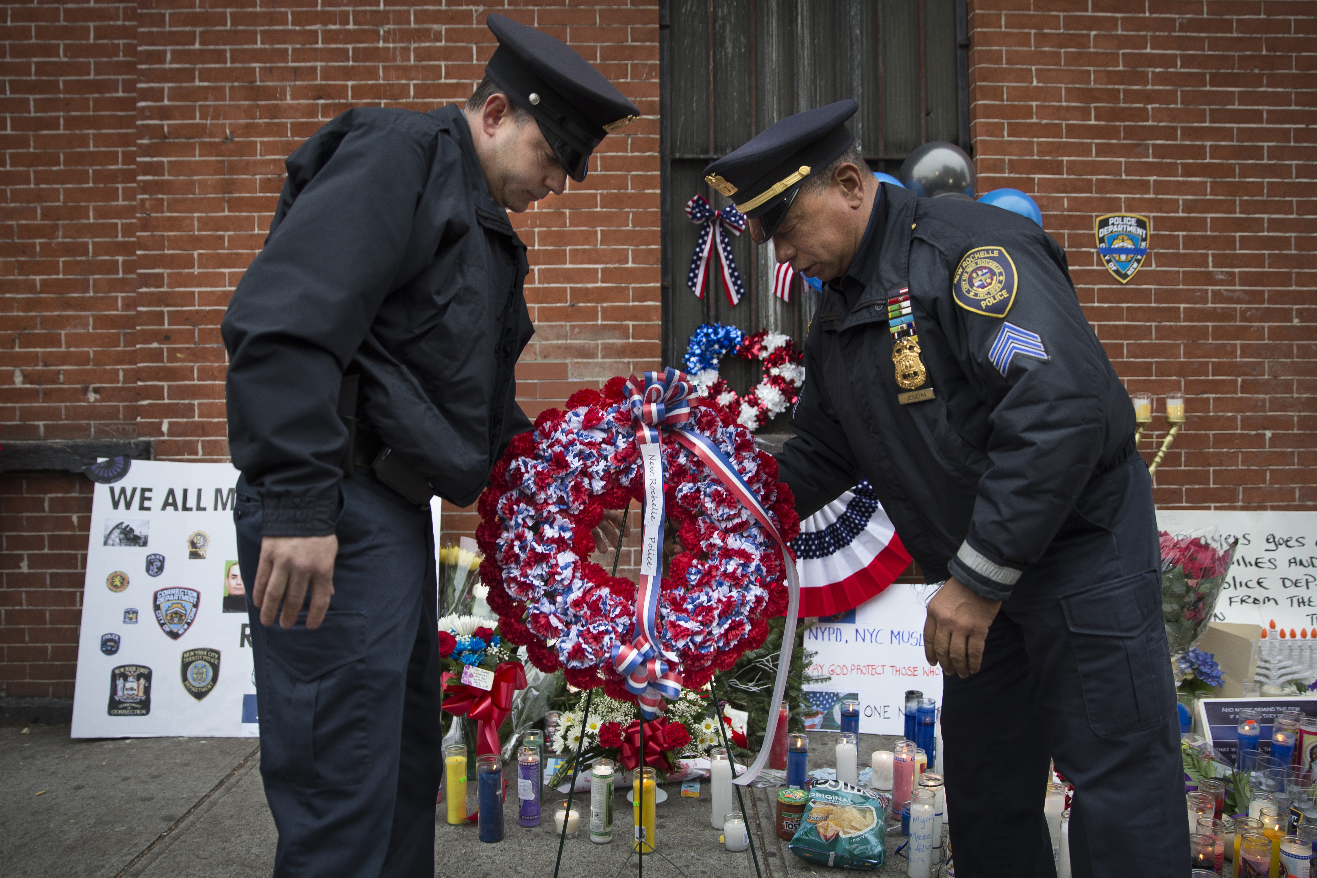 In this file photo, members of the New Rochelle, N.Y. police department place a wreath at a makeshift memorial near the site where NYPD officers Rafael Ramos and Wenjian Liu were murdered in the Brooklyn borough of New York, Dec. 22, 2014.