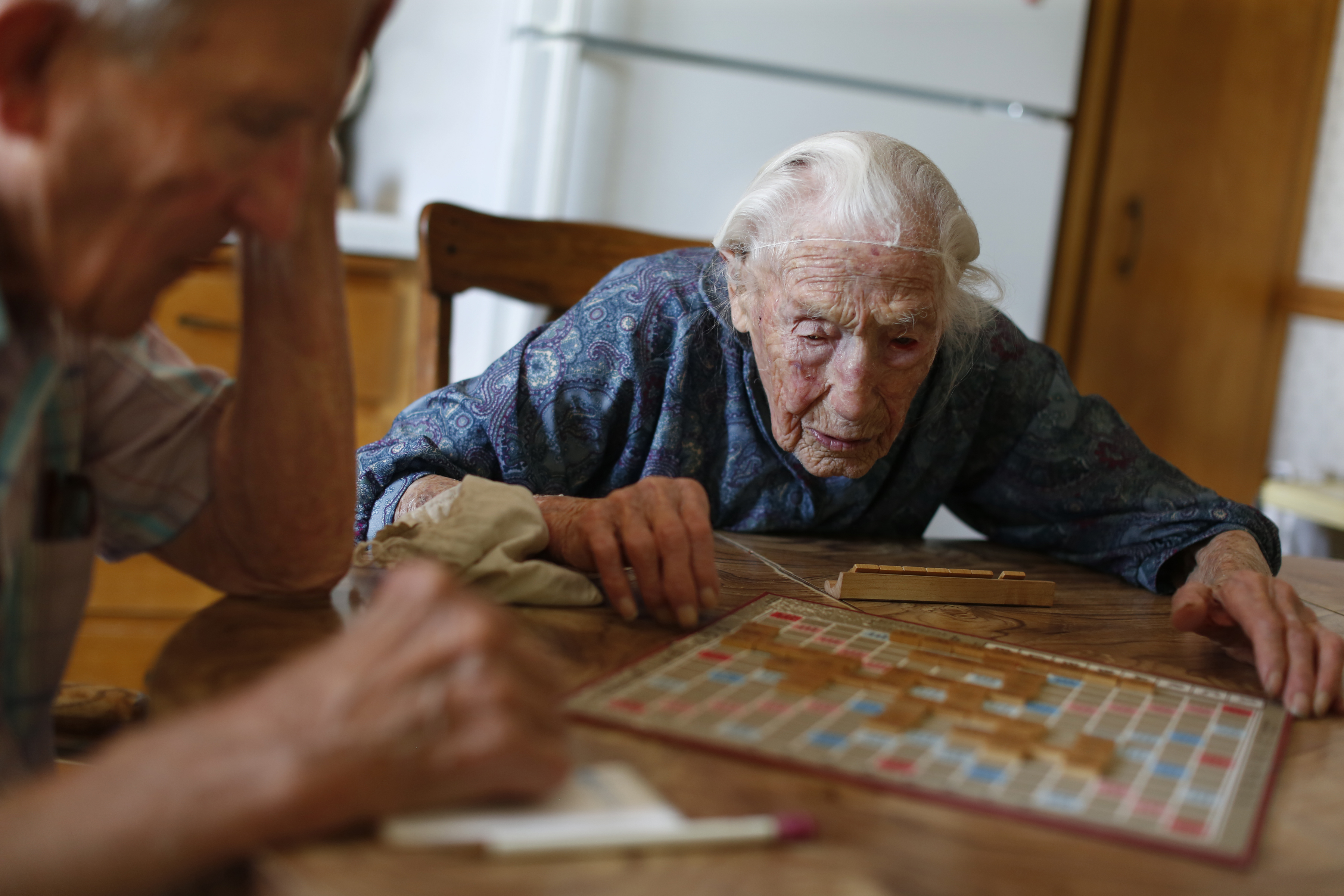 At her home in Pottsdam, Minn., Anna Stoehr plays Scrabble with her son Harlan, 83, who is changing the hoses on her washer