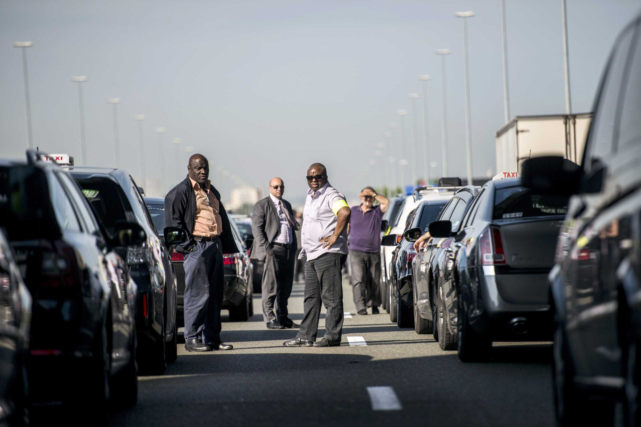 Taxis drivers block a highway outside Paris, near Roissy on June 11, 2014, as they take part in a demonstration to protest the growing number of minicabs, known in France as Voitures de Tourisme avec Chauffeurs (VTC).