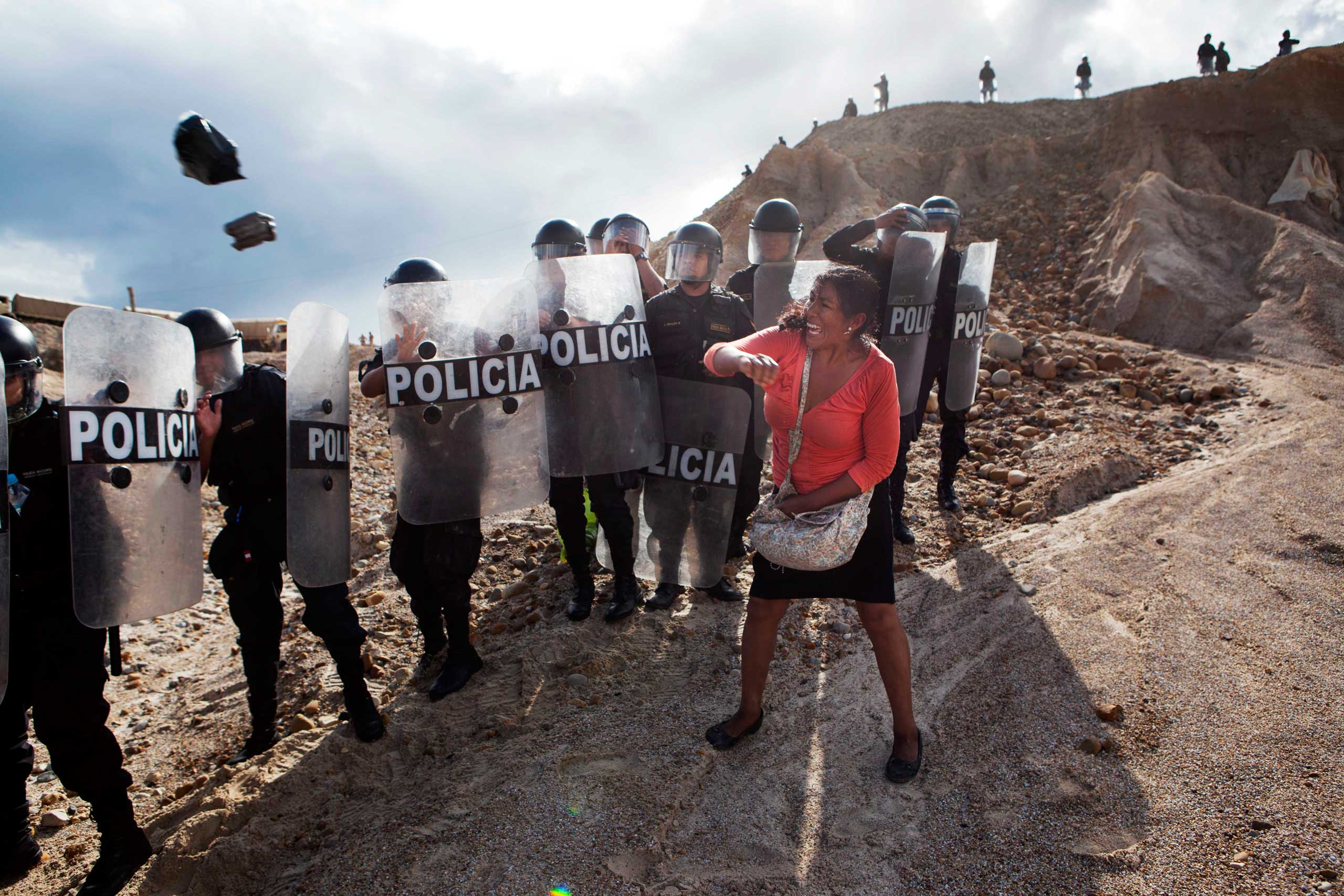 Peru: Protest against government's crackdown on illegal gold mining.A woman throws a rock and a bag at police blocking her from getting home in the Huepetuhe district of the Madre de Dios region of Peru., April 28, 2014.