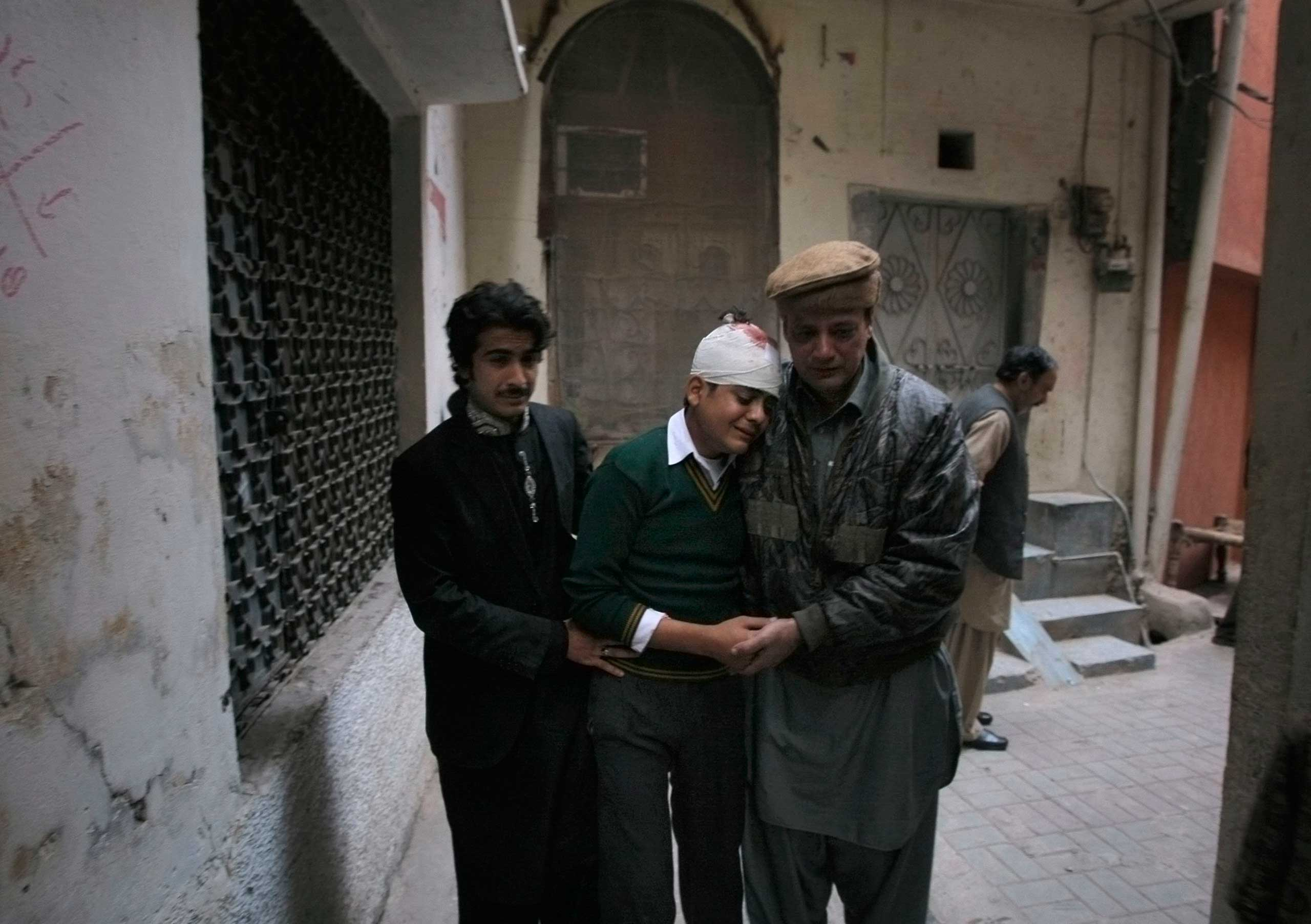 The uncle and cousin of injured student Mohammad Baqair, center, comfort him as he mourns the death of his mother who was a teacher at the school which was attacked by Taliban, in Peshawar, Pakistan on Dec. 16, 2014.