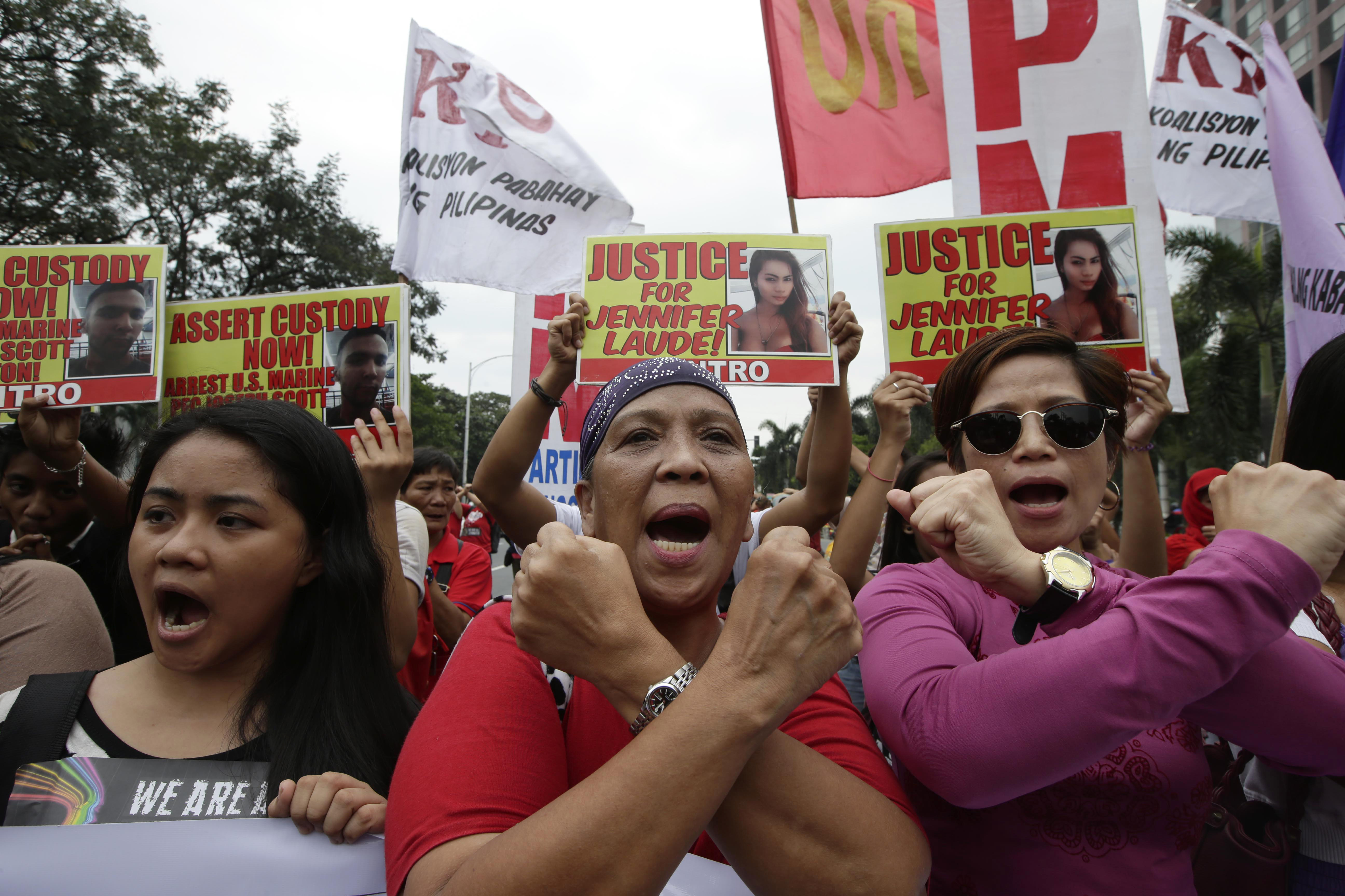 Protesters make cross signs as they shout slogans during a rally outside the U.S. Embassy in Manila, Philippines, Nov. 24, 2014 to demand justice for the Oct. 11 killing of Filipino transgender Jennifer Laude at the former US naval base of Subic.