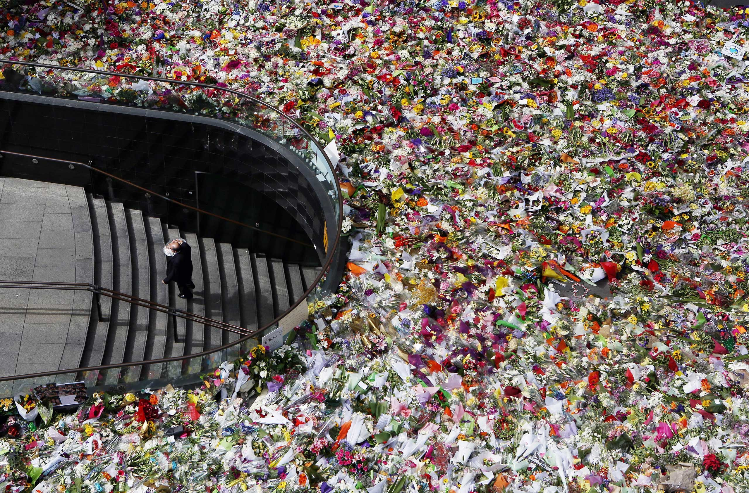 Dec. 18, 2014. A man arrives with a bunch of flowers in Martin Place in Sydney, Australia. Tens of thousands of Sydneysiders have paid tribute to the two victims of the Martin Place siege, barrister Katrina Dawson and cafe manager Tori Johnson.