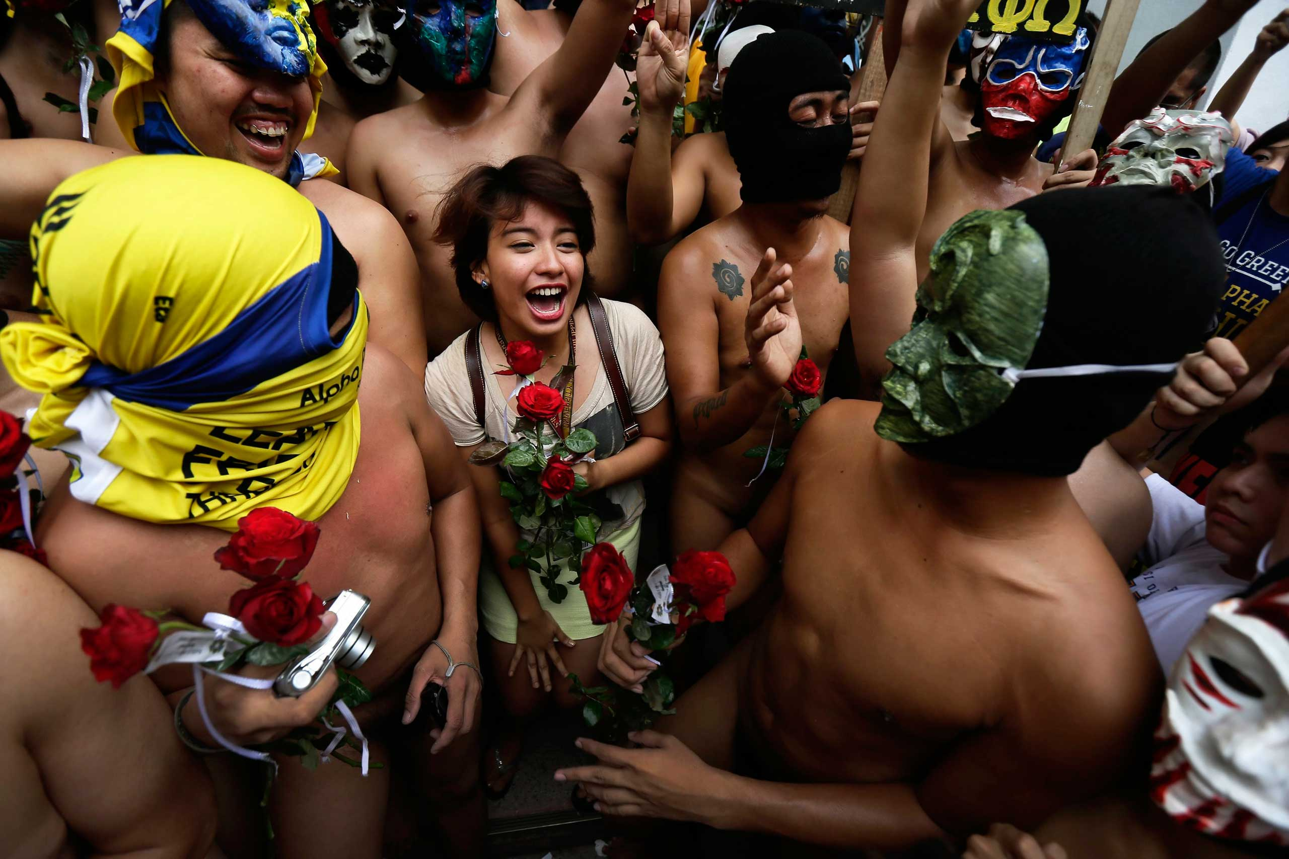 Dec. 12, 2014. Filipino student Katrina Tapia (C) reacts while being surrounded by members of Alpha Phi Omega (APO) fraternity during the annual 'Oblation run' inside the University of the Philippines in Diliman, eastern Manila, Philippines.
