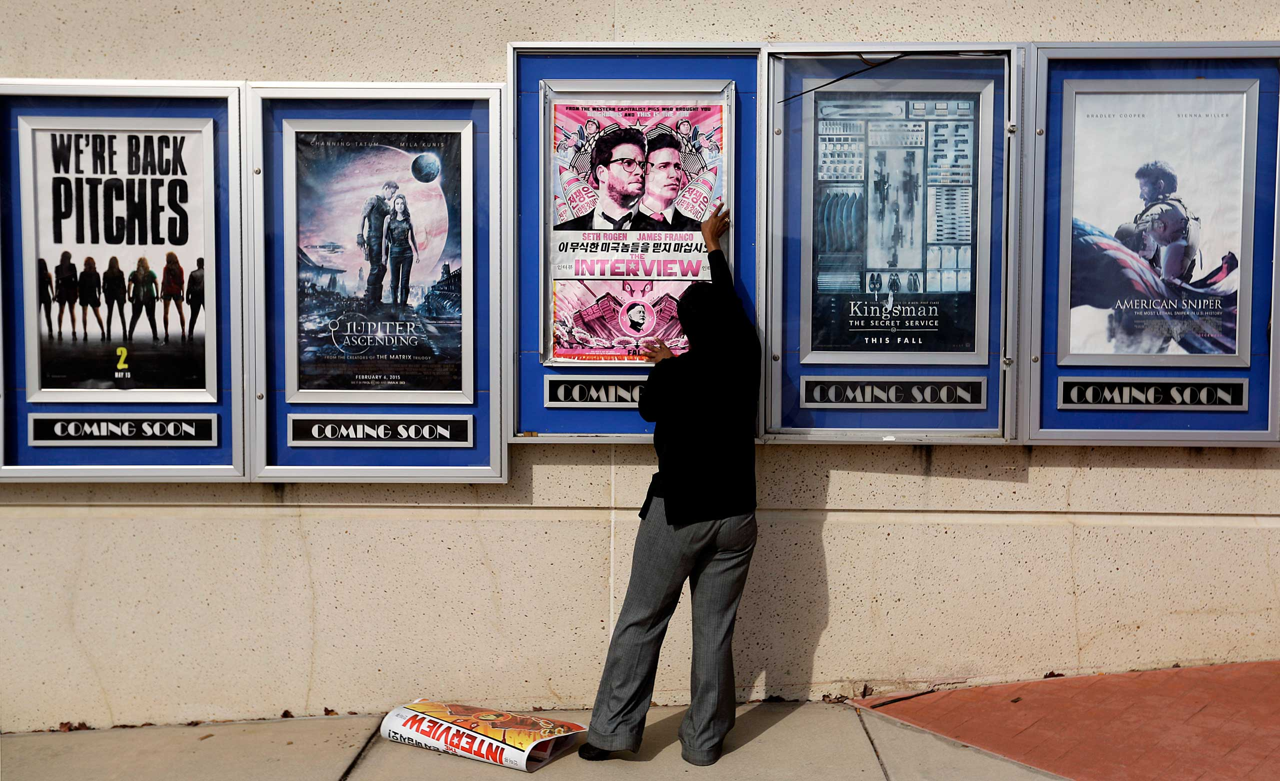 Dec. 17, 2014. A poster for the movie  The Interview  is taken down by a worker after being pulled from a display case at a Carmike Cinemas movie theater, Wednesday, Dec. 17, 2014, in Atlanta. Georgia-based Carmike Cinemas has decided to cancel its planned showings of  The Interview  in the wake of threats against theatergoers by the Sony hackers.