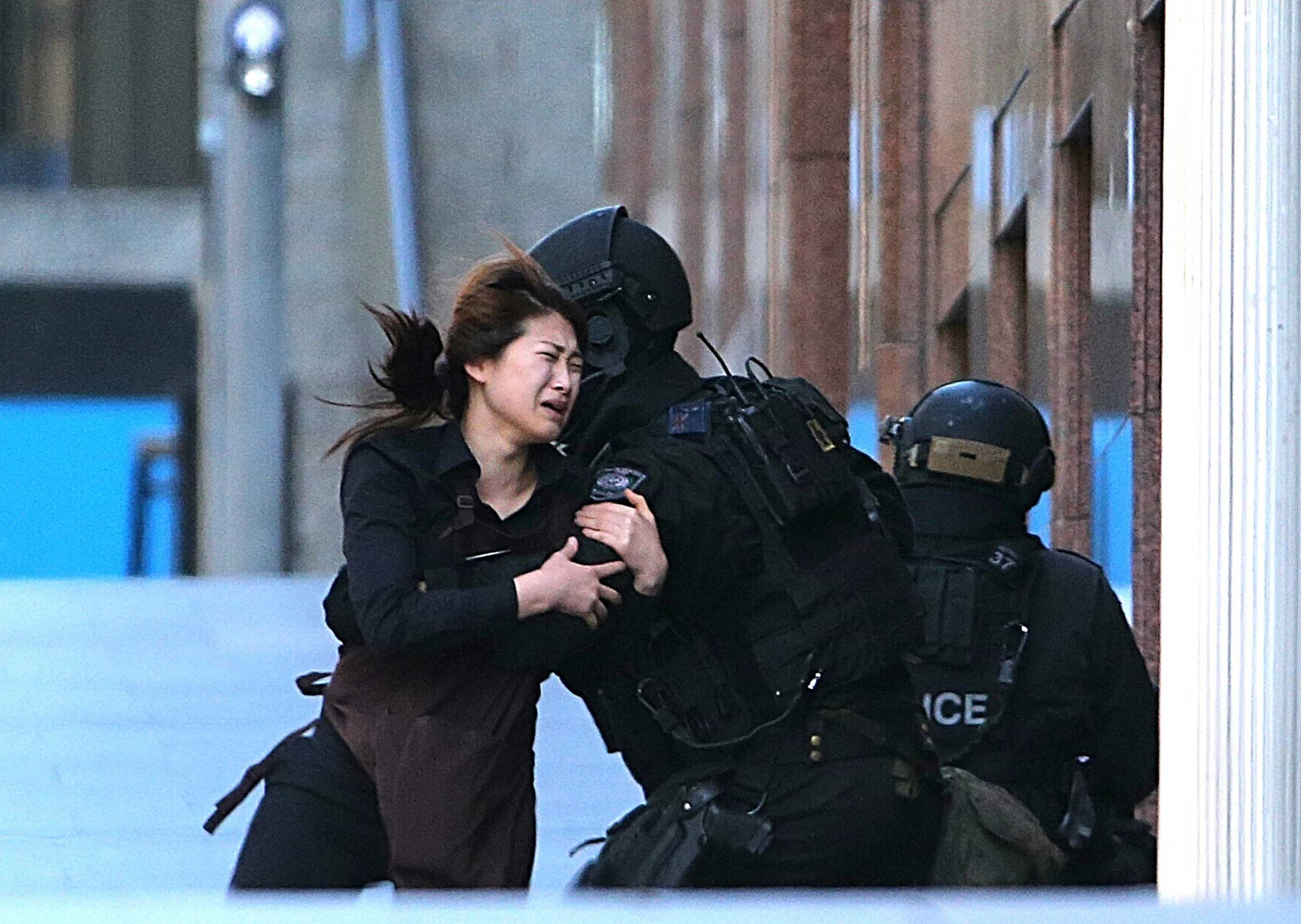 Dec. 15, 2014. A hostage runs to armed tactical response police officers for safety after she escaped from a cafe under siege at Martin Place in the central business district of Sydney, Australia.