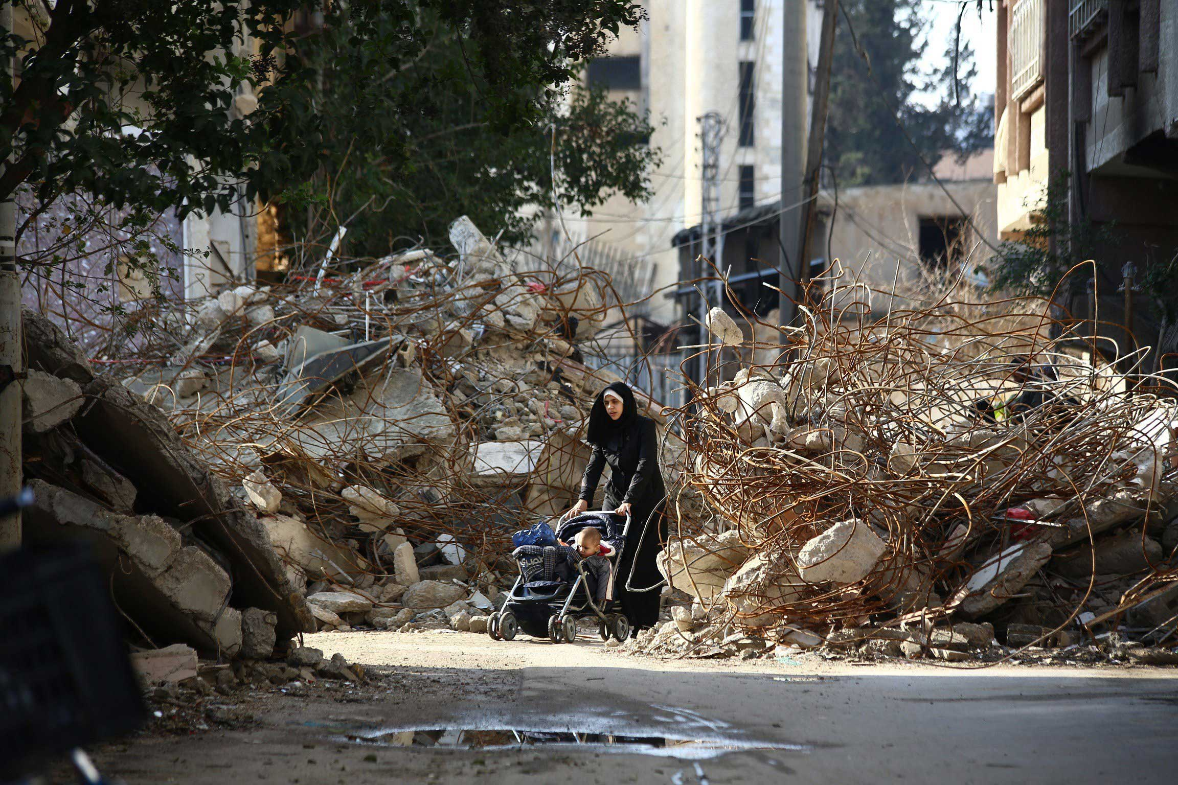 Dec. 13, 2014. A woman walks pushing a pram between the rubble of destroyed buildings in the besieged rebel bastion of Douma, Syria.