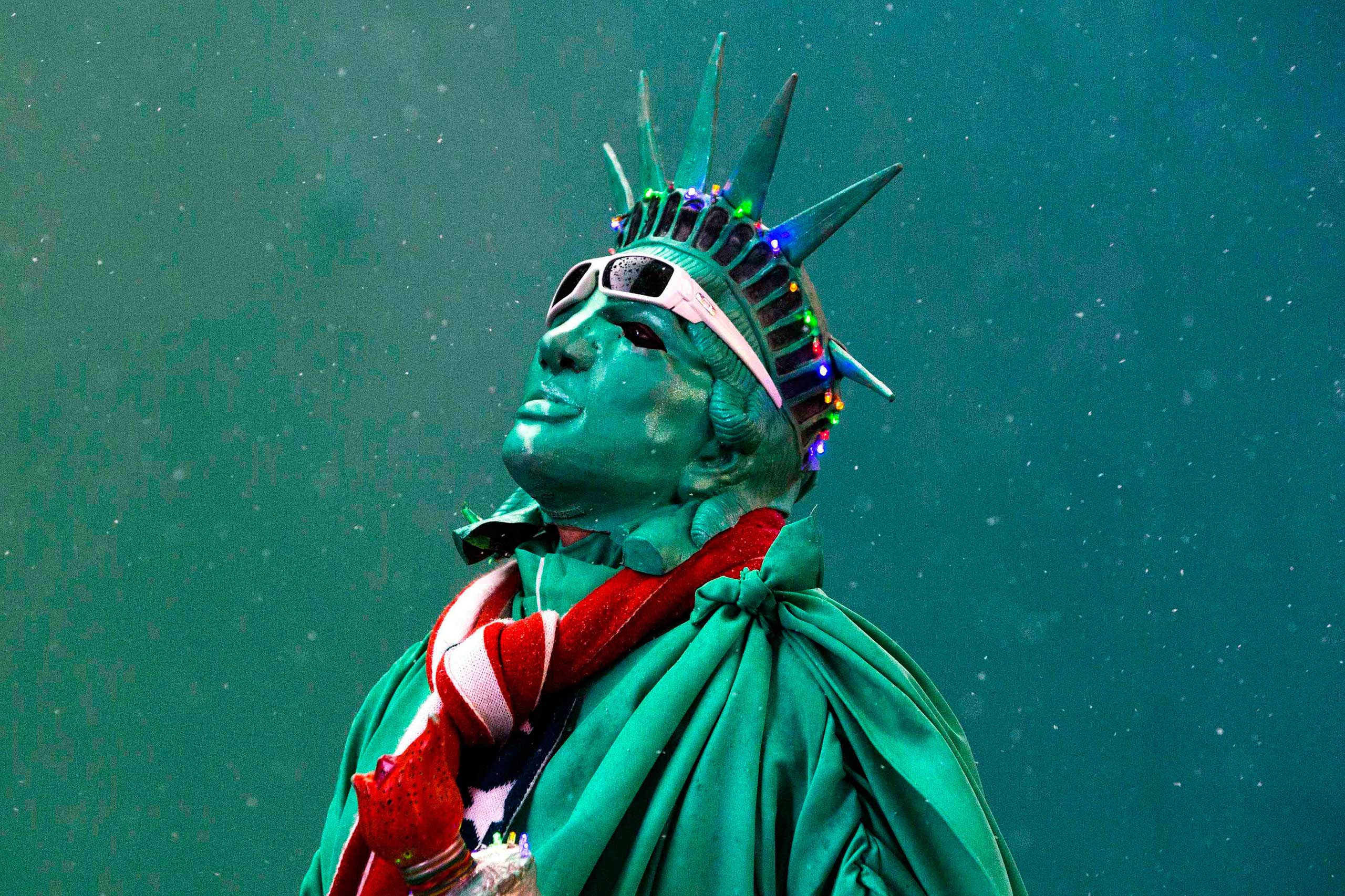 A street performer dressed as the Statue of Liberty stands among light snow in Times Square in New York, Dec. 10, 2014.