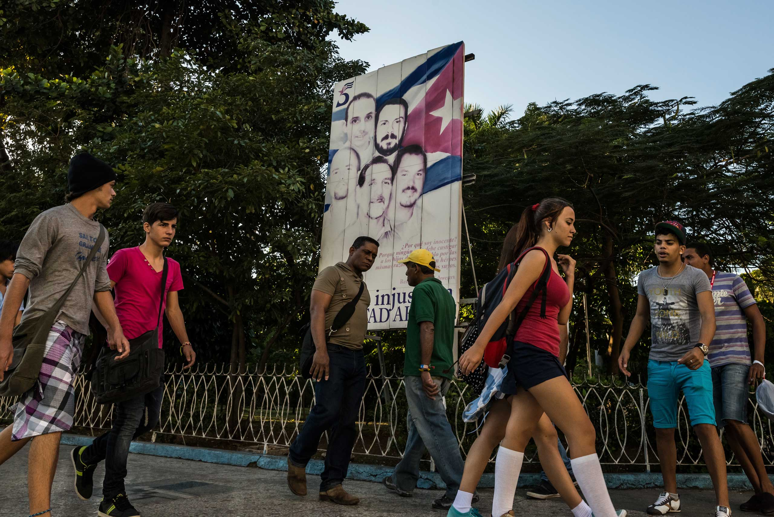 Dec. 18, 2014. People pass a poster calling for the release of the Cuban Five spies, the last of who were released the day before, in Havana, Cuba.