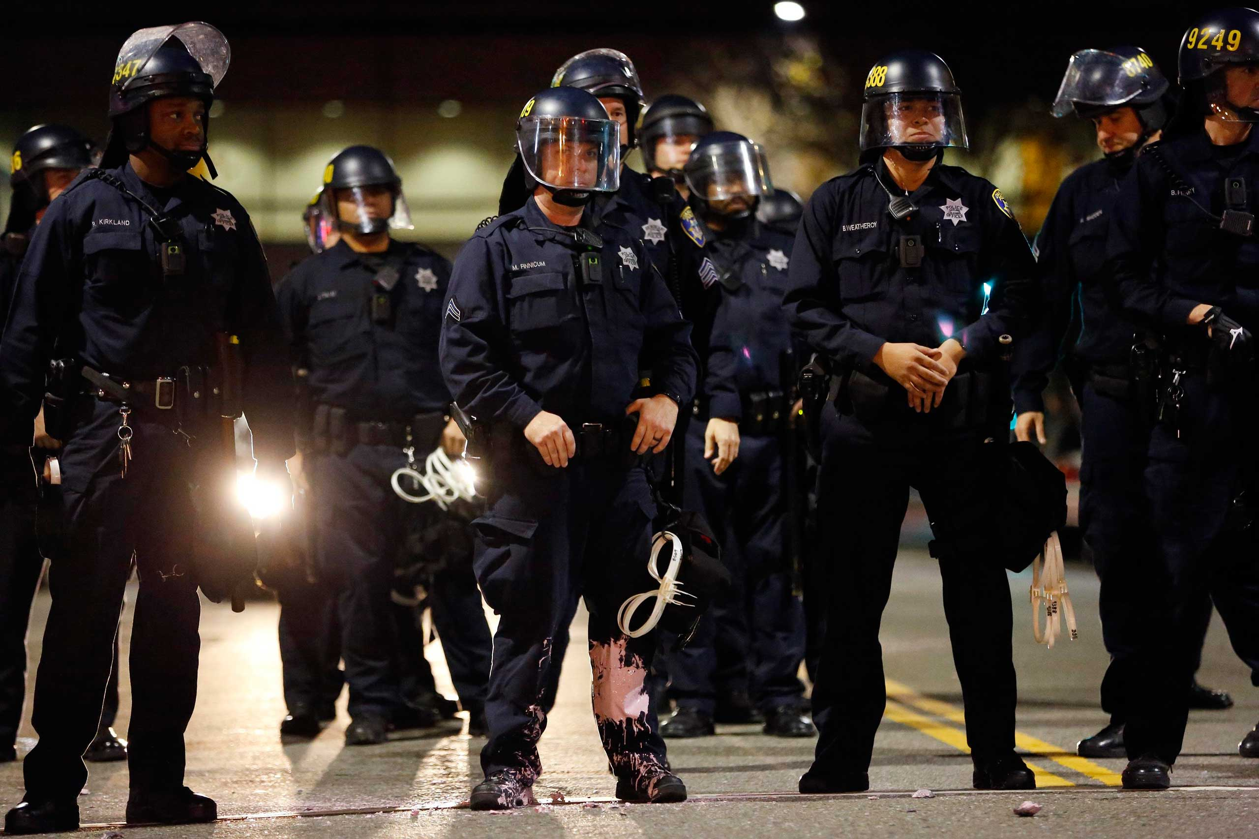 A police officer looks into the crowd, after he was hit on the leg with paint thrown by protesters during an evening demonstration against police violence in Oakland, Calif. on Dec. 13, 2014.