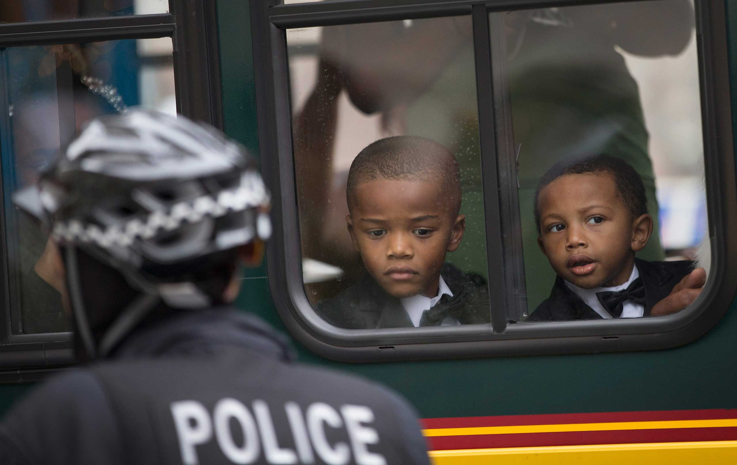 Young boys watch from a seat in a charter bus as demonstrators march along Michigan Avenue to protest police brutality on Dec. 13, 2014 in Chicago.