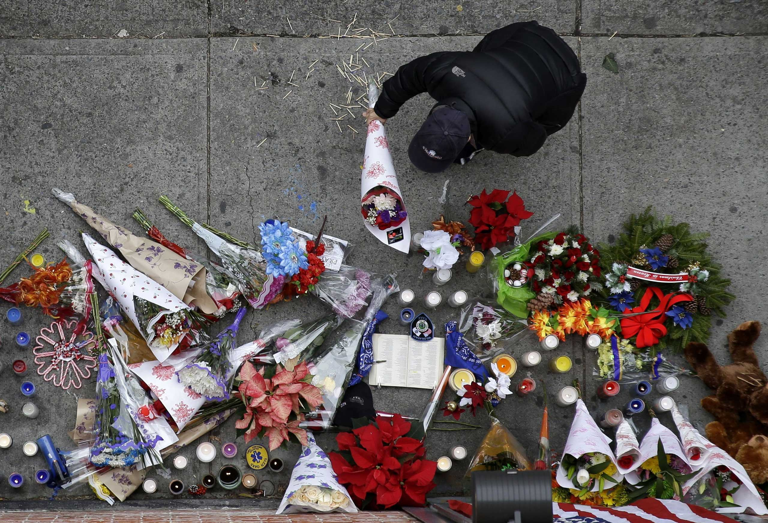 A man leaves flowers at an impromptu memorial near the site where two police officers were killed the day before in the Brooklyn borough of New York City on Dec. 21, 2014.
