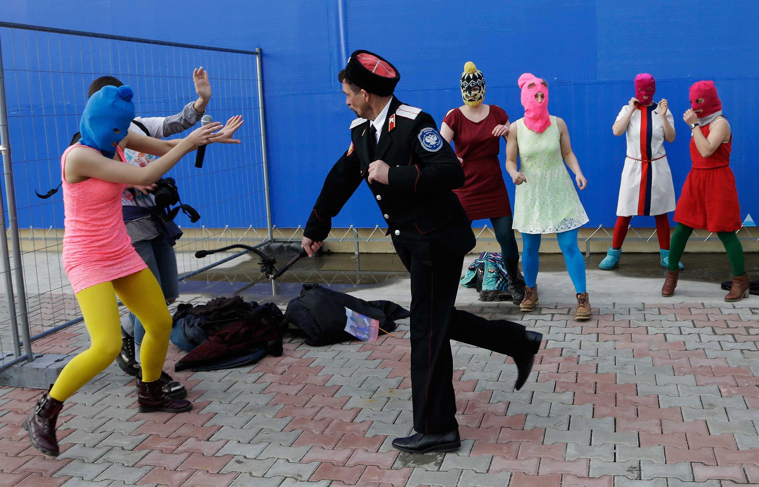 Russia: Protest performance at Sochi OlympicsA Cossack militiaman attacks Nadezhda Tolokonnikova and a photographer as she and fellow members of the punk group Pussy Riot, including Maria Alekhina, center, in the pink balaclava, stage a protest performance in Sochi, Russia, Feb. 19, 2014.