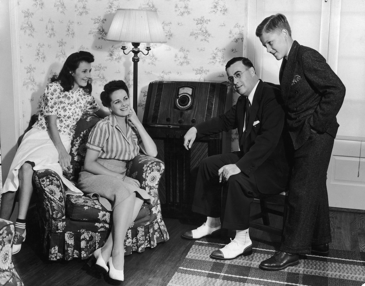Circa 1945,  a family of four gathers in their living room to listen to their home radio set