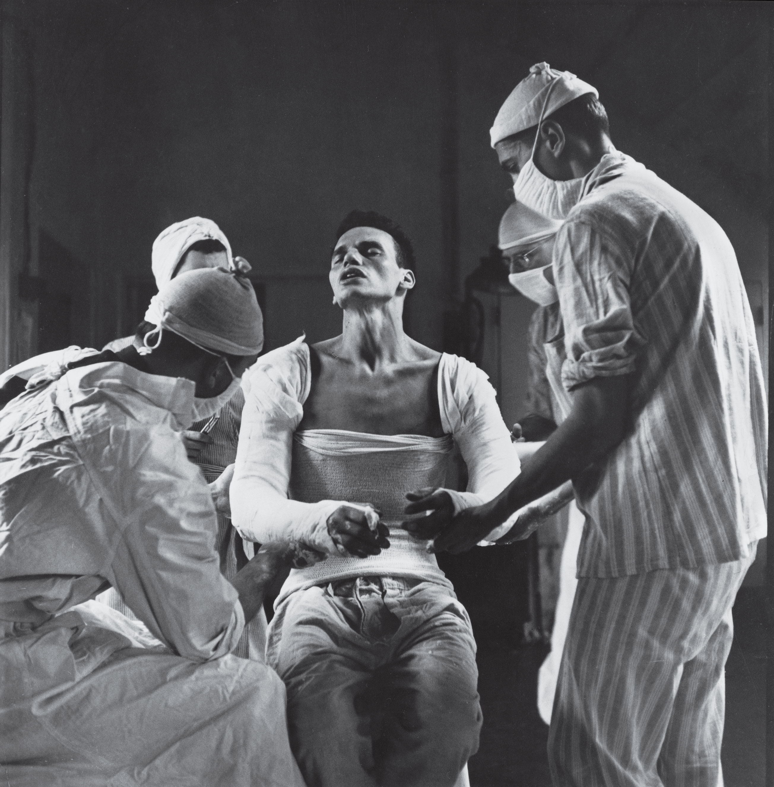 George Lott, 22, a medic attached to a battalion aid station of the 137th Infantry Regiment in Patton's Third Army, was wounded in both arms by German mortar fire in France in 1944. Here, he suffers as doctors mold a plaster cast to his body.