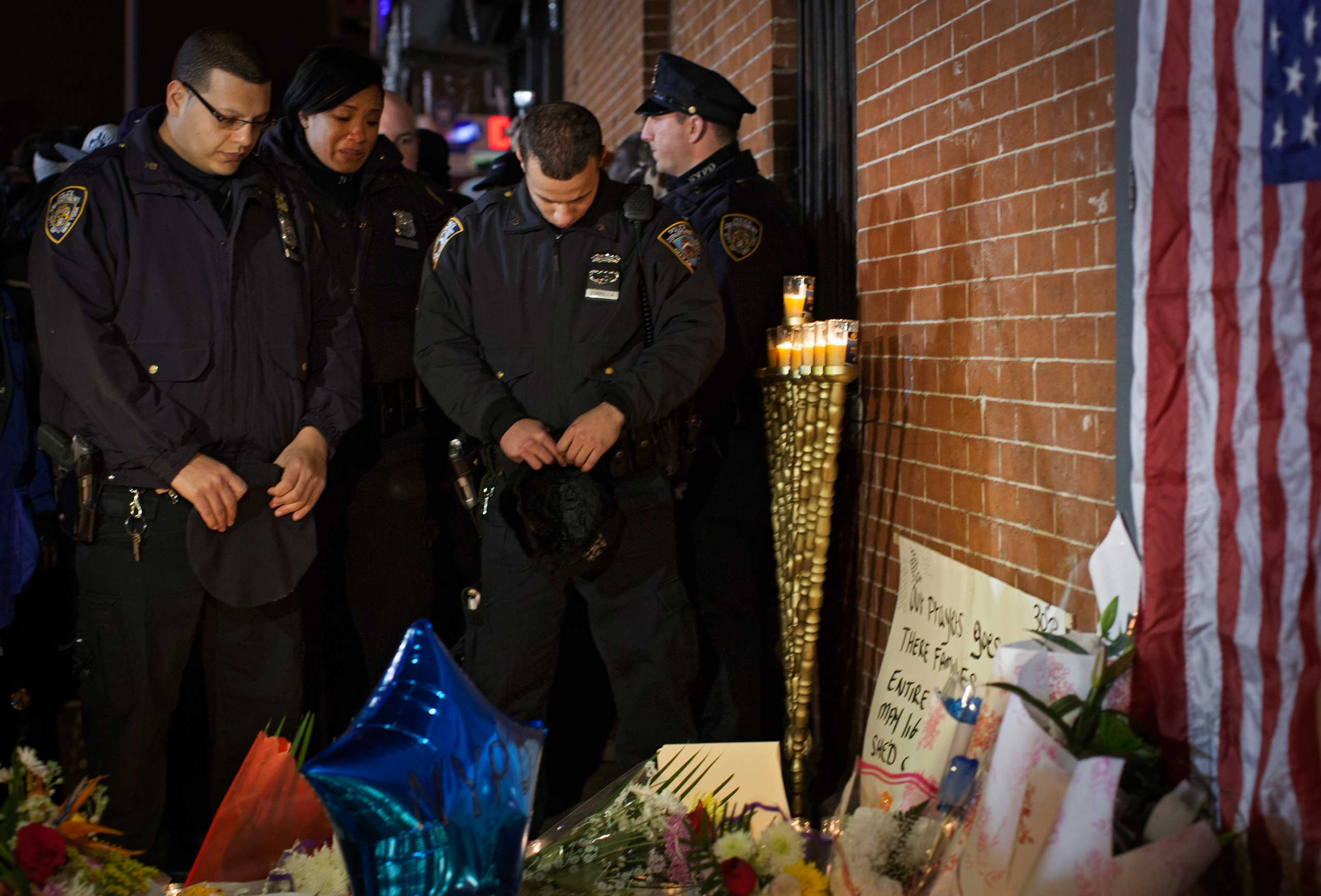 Police officers pause in front of a memorial for two police officers who were killed in Brooklyn on Dec. 21, 2014.