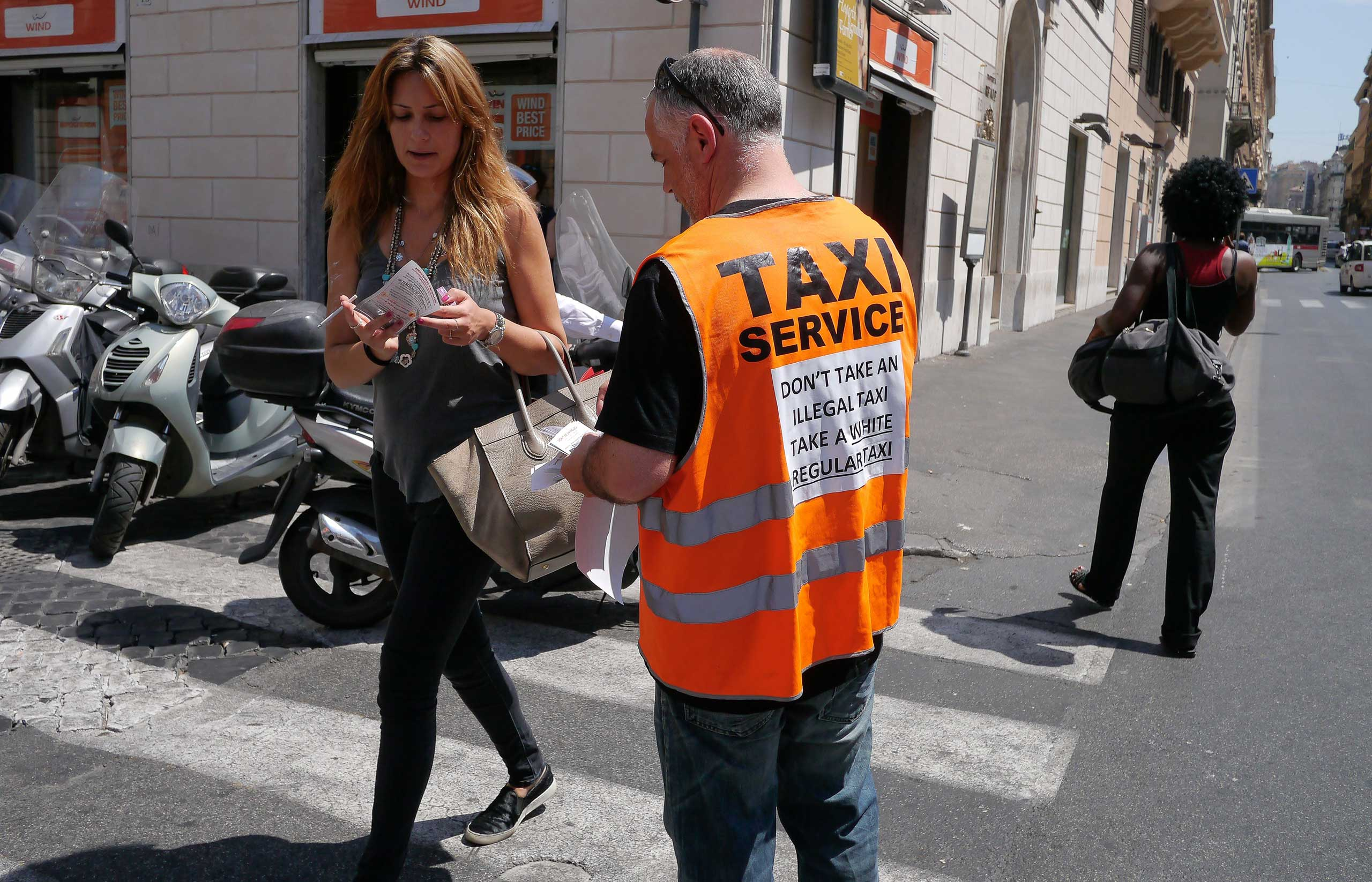 "An Italian taxi driver distributes leaflets reading ""Don't take an illegal taxi, take a white regular taxi"" during a protest on June 11, 2014 in Rome."
