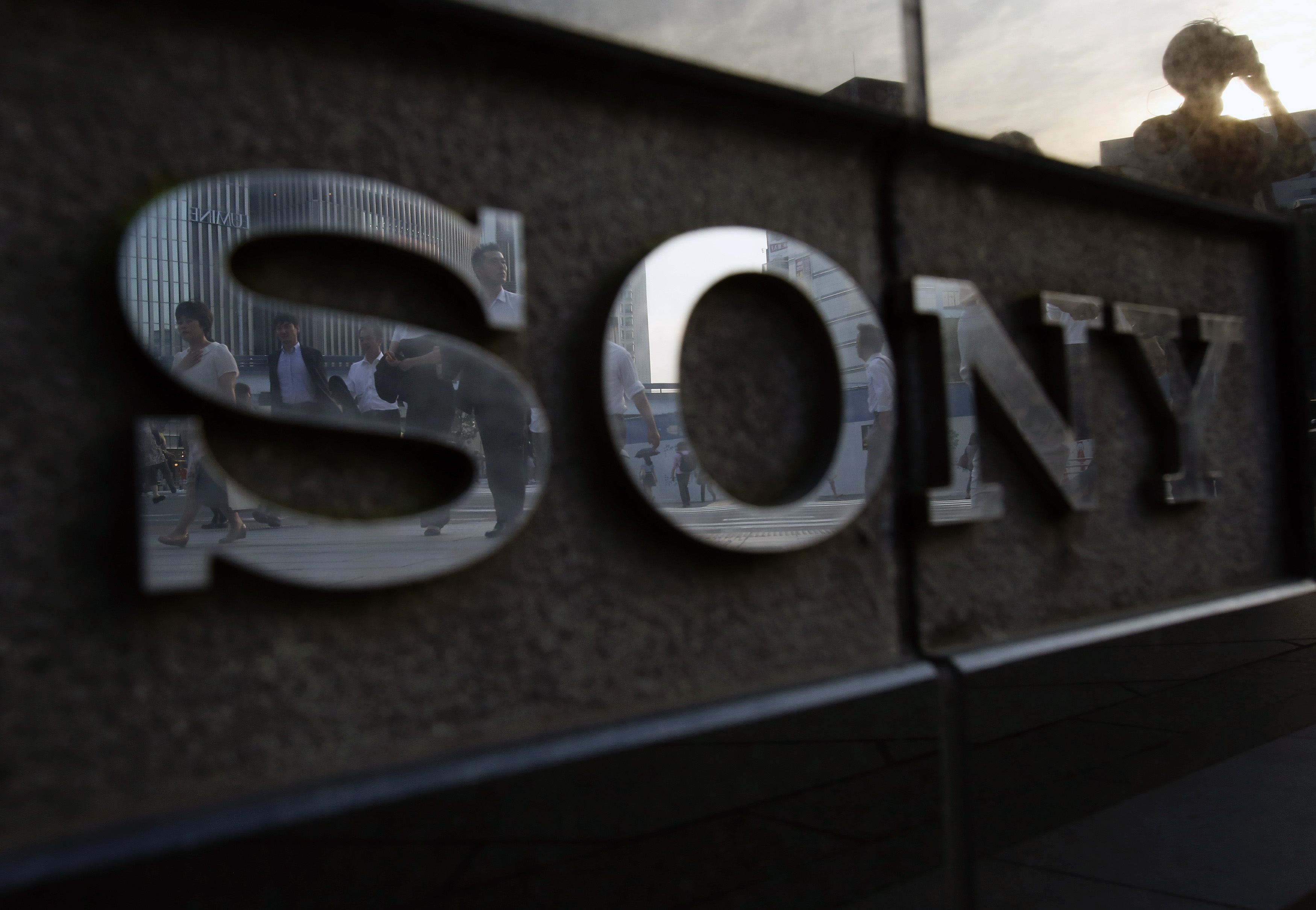 Pedestrians are reflected in a logo of Sony Corp outside its showroom in Tokyo July 16, 2014.