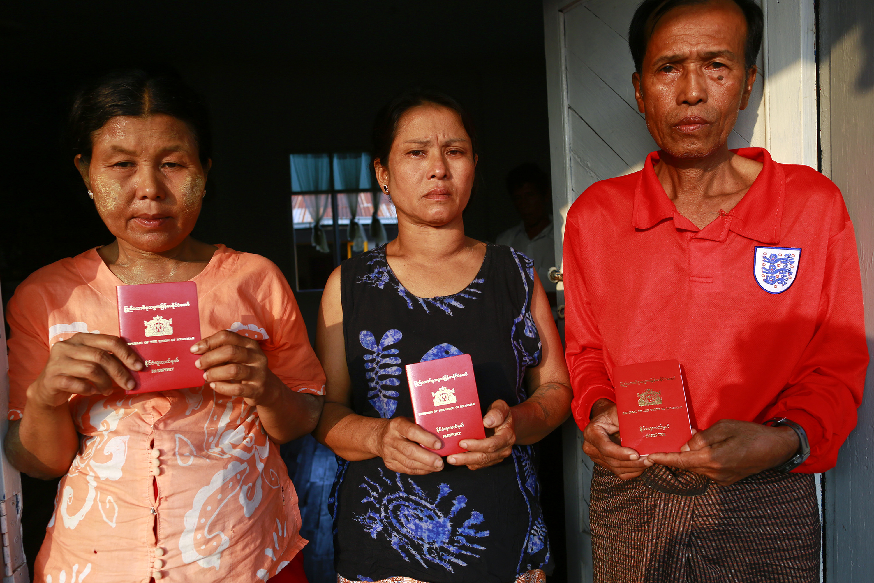 Parents of Burmese workers suspected of killing British tourists in Thailand show their passports as at a monastery outside Rangoon on Oct. 16, 2014