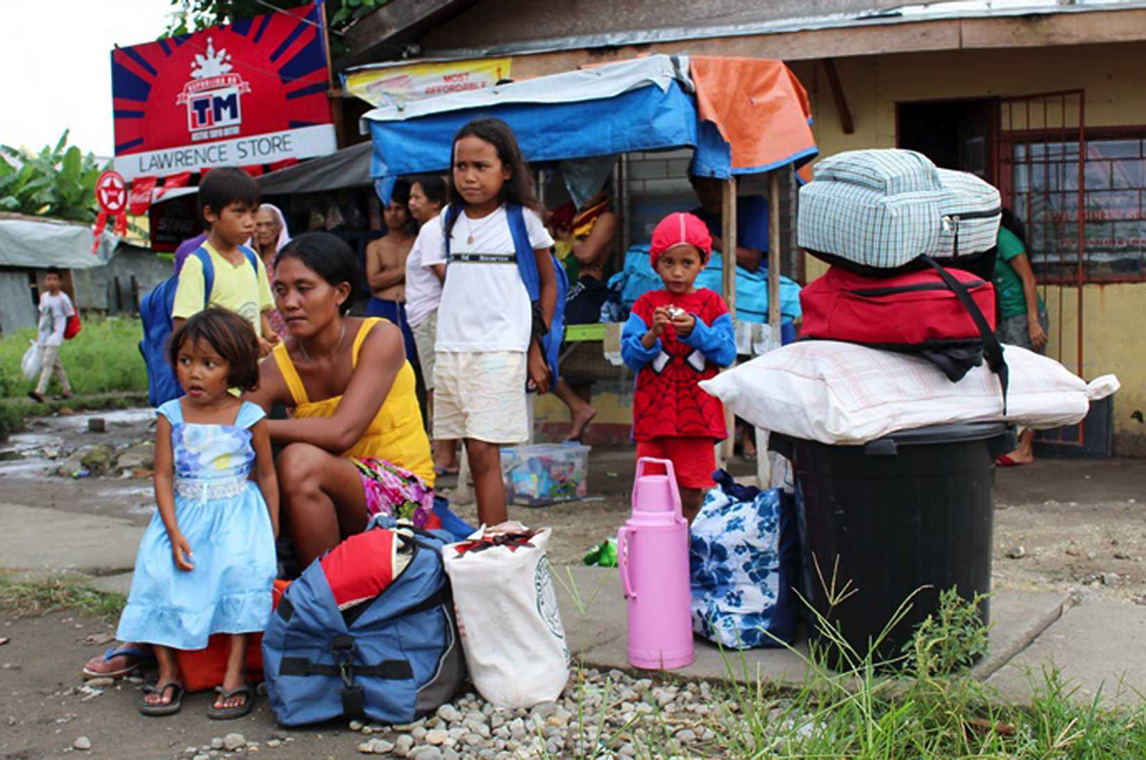 Residents with their belongings wait for a government vehicle to bring them to the evacuation center in Tacloban city, central Philippines, on Dec. 4, 2014