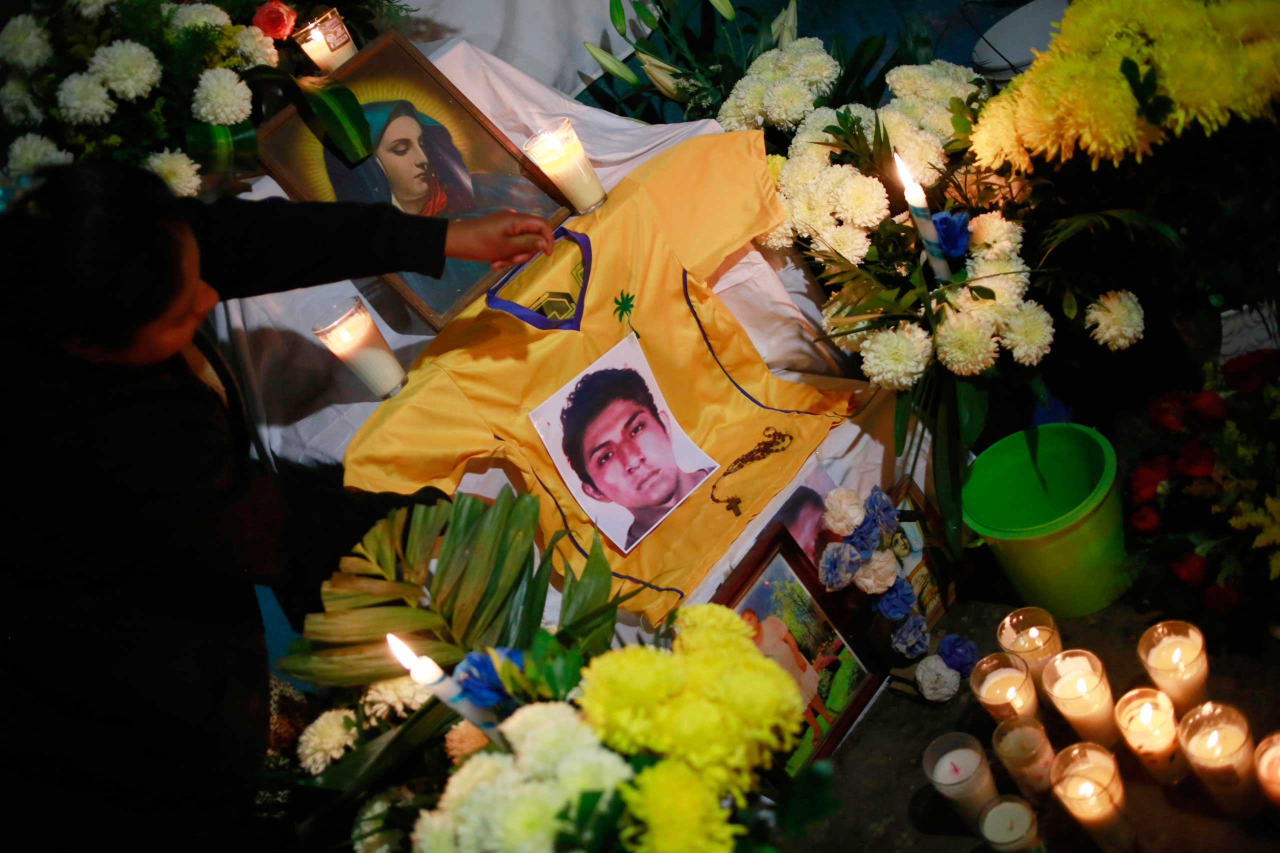 A photo of Alexander Mora Venancio is seen at an altar in the house of his father in El Pericon, in the southern Mexican state of Guerrero, Dec. 6, 2014.