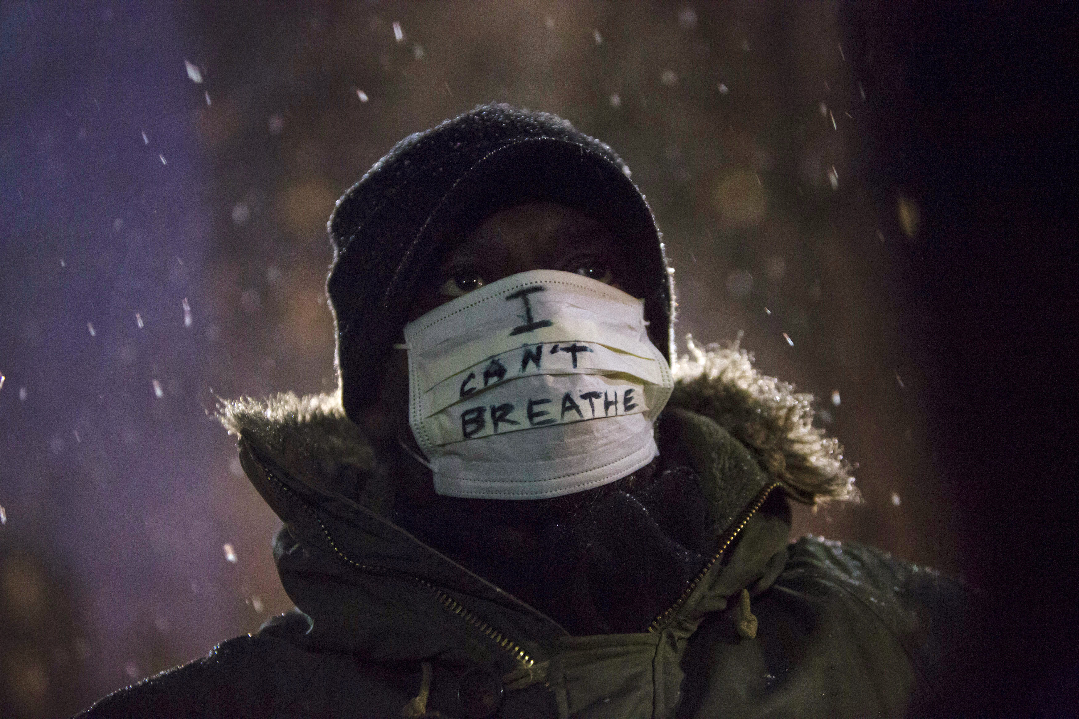 A man stands in falling snow following a news conference where members of Justice League NYC presented a list of demands at City Hall in New York Dec. 10, 2014