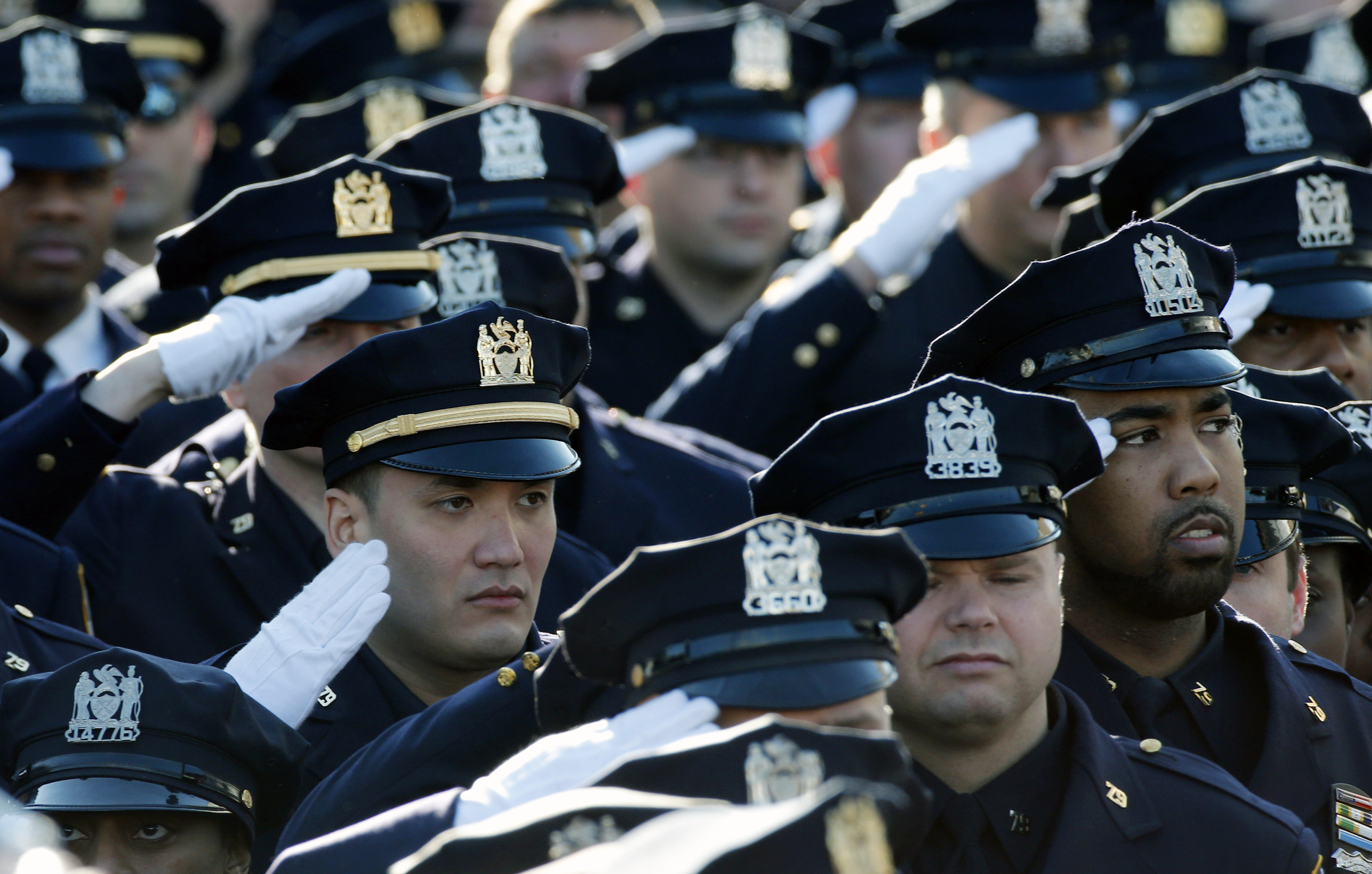Police salute during the playing of the U.S. national anthem outside the Christ Tabernacle Church in New York City at the start of the funeral service for slain New York Police Department officer Rafael Ramos on Dec. 27, 2014