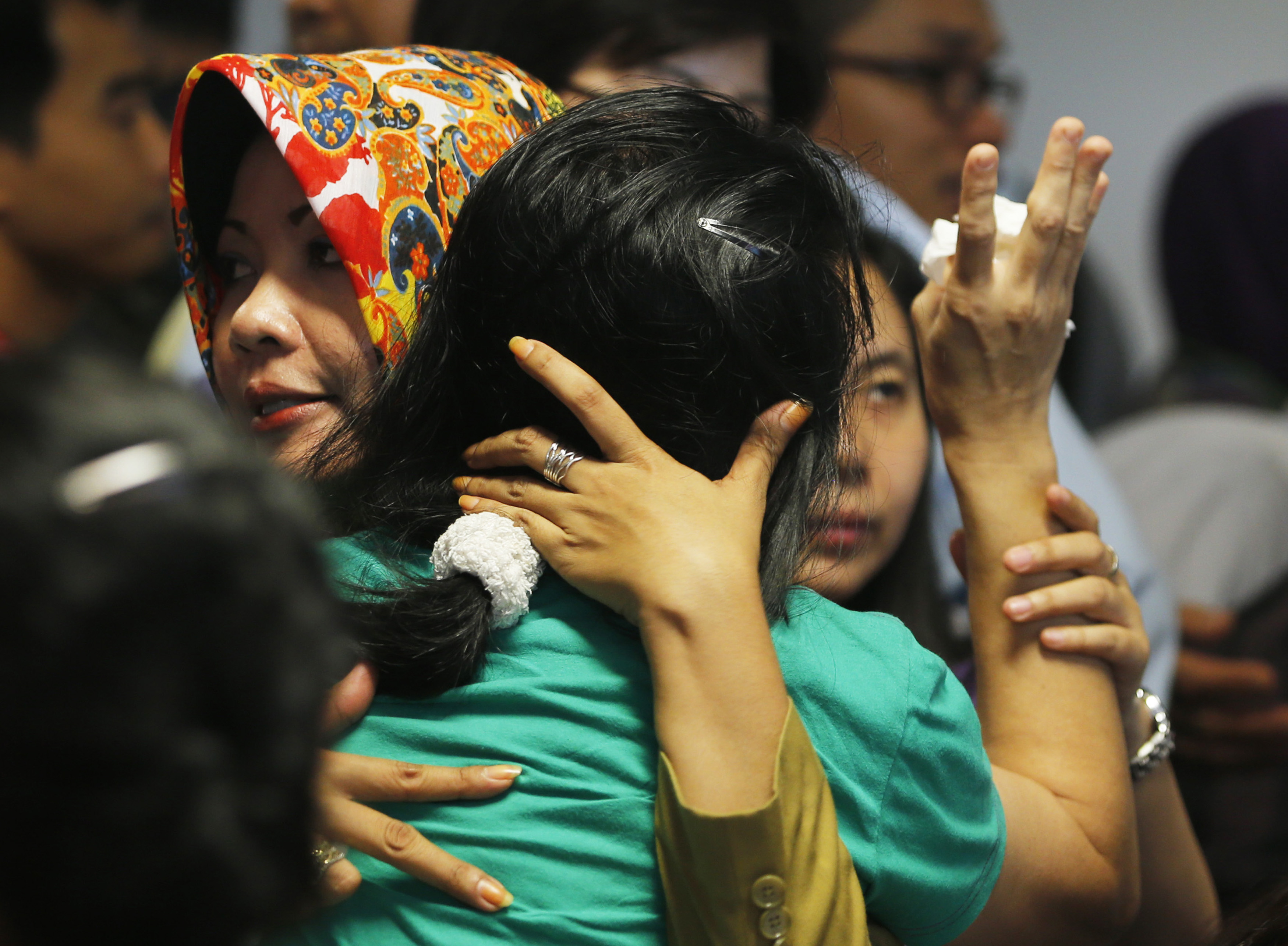 A government official, left, tries to calm a family member of passengers on board AirAsia Flight QZ 8501 at a waiting area in Juanda International Airport in Surabaya, Indonesia, on Dec. 30, 2014