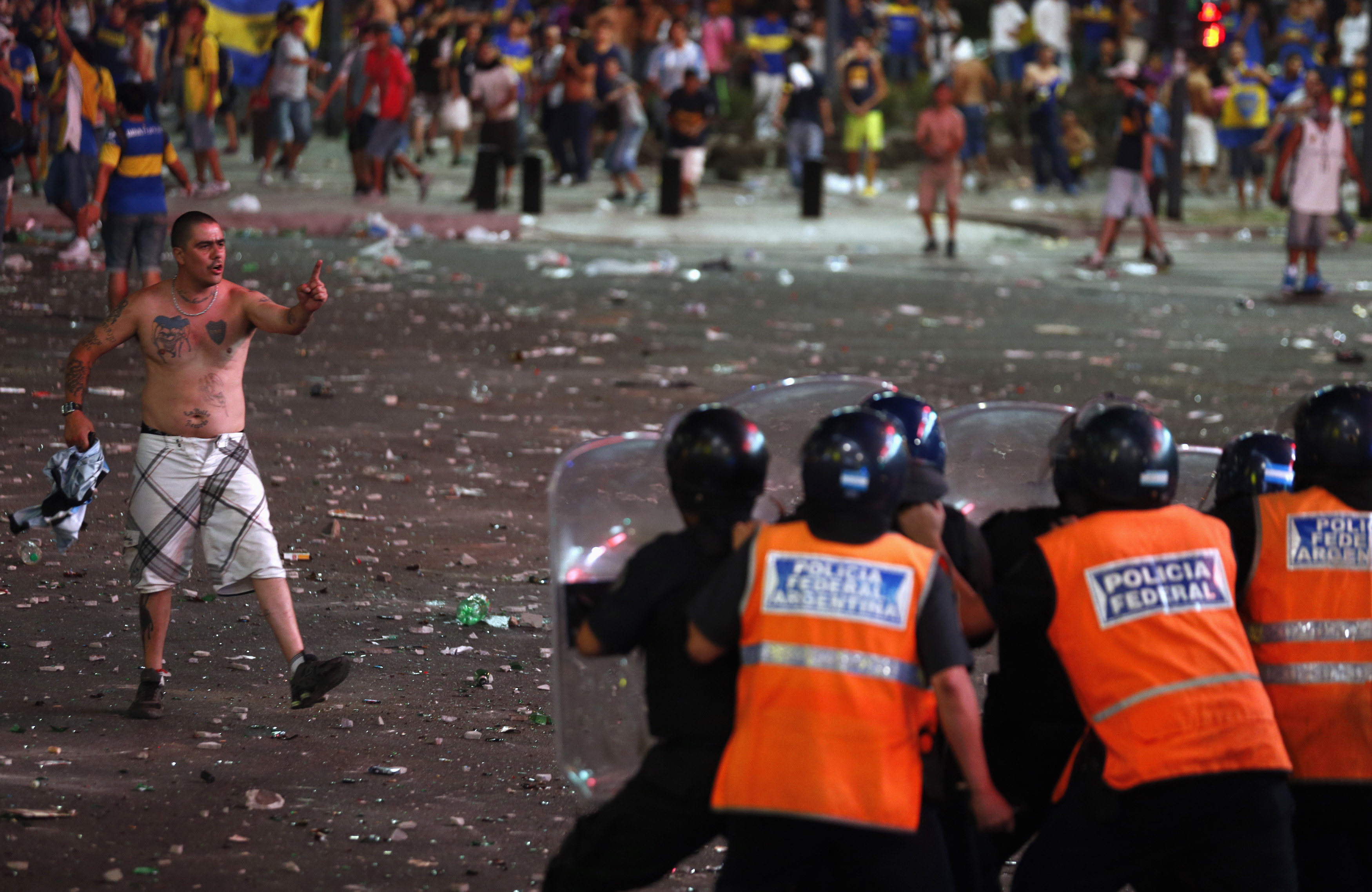 A fan of Argentine soccer team Boca Juniors confronts police during riots after celebrations of Boca Juniors Fan Day in downtown Buenos Aires December 12, 2013.
