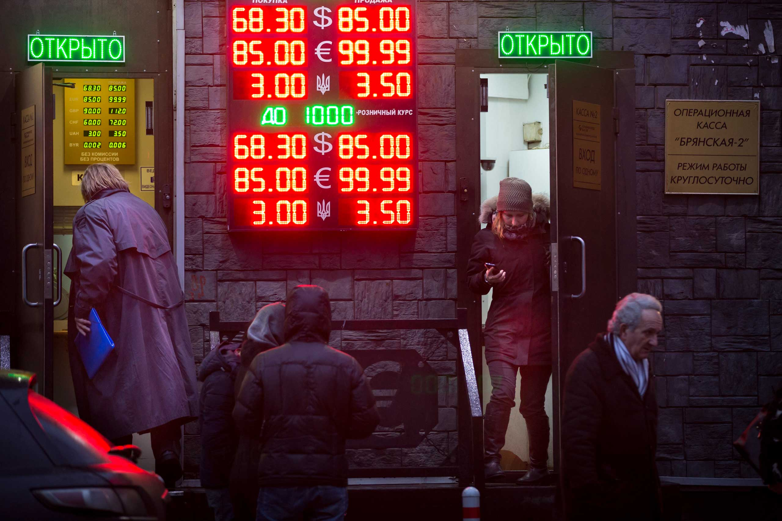 People wait to exchange their currency as  signs advertise the exchange rates at a currency  exchange office in Moscow, Dec. 16, 2014.