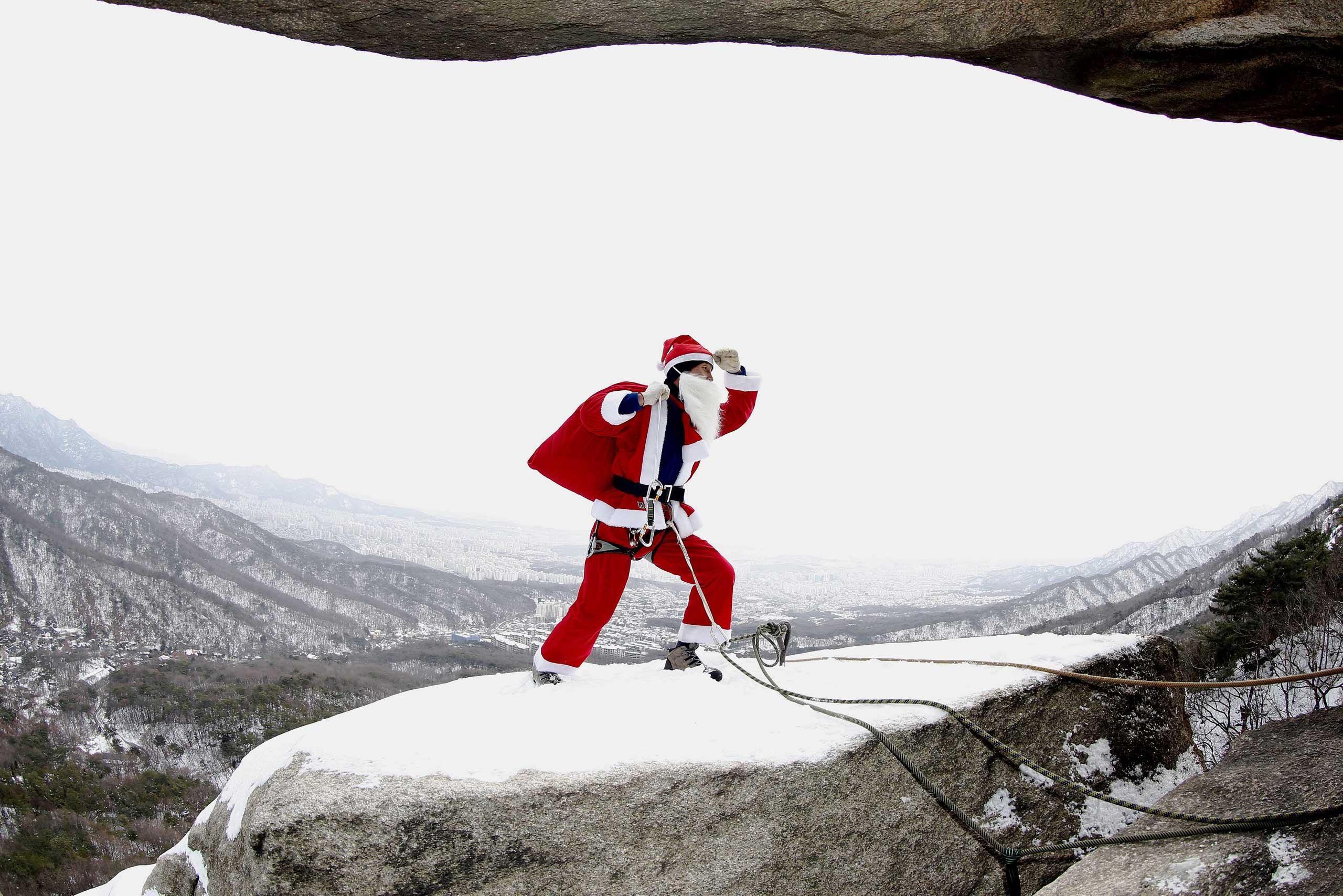 Kim Chang-Gon dressed as Santa Claus rock-climbs during an event marking the Christmas holiday season on Buckhan mountain near Seoul, South Korea on Dec. 21, 2014.