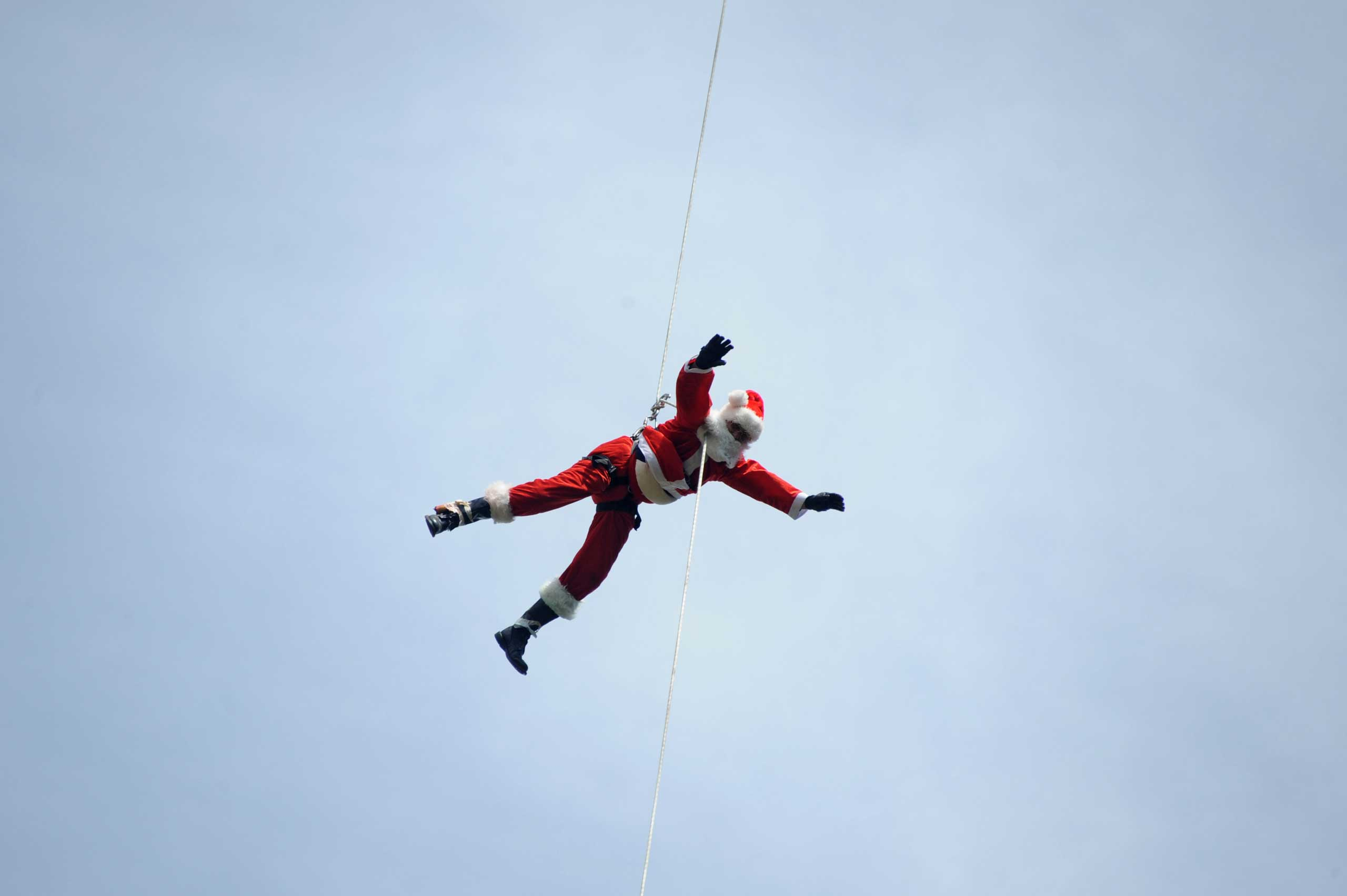 Guatemalan firefighter Hector Chacon dressed as Santa Claus goes down a cable from a bridge to deliver presents to children in Guatemala City on Dec. 21, 2014.