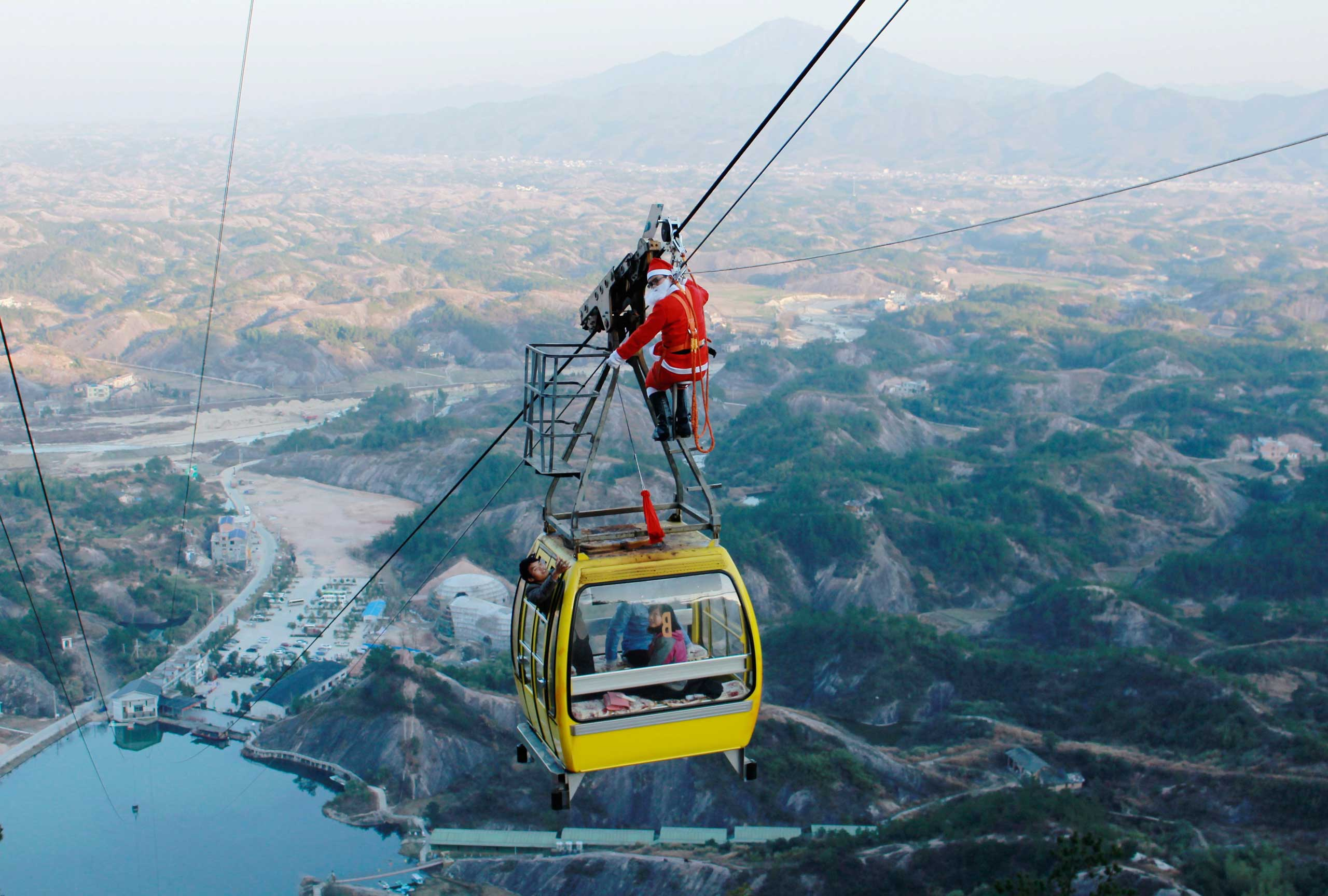 A worker dressed as a Santa Claus delivers gifts to tourists in the cable car ahead of Christmas Day celebrations  in Pingjiang county in China's Hunan province.