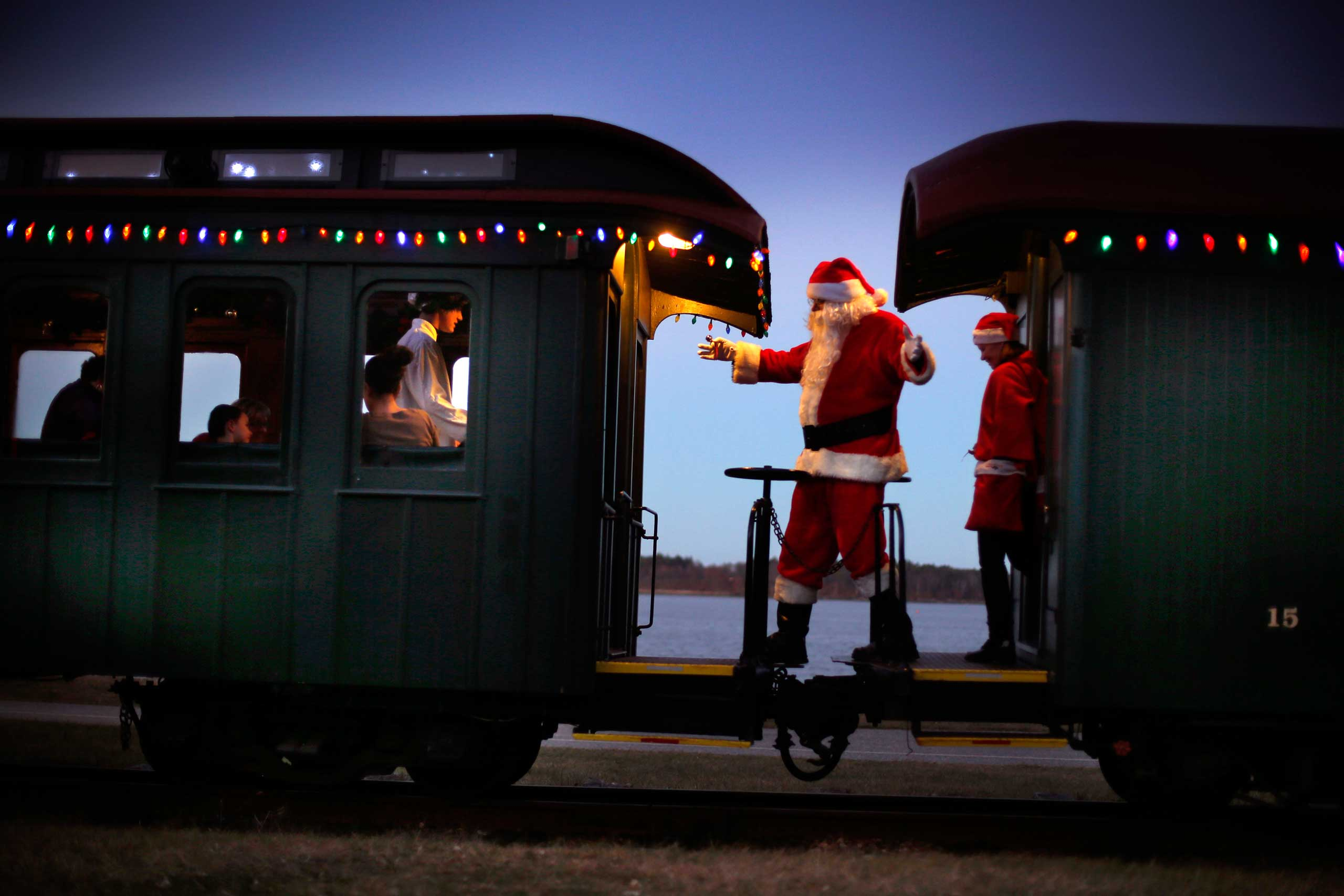 A man portraying Santa Claus moves between cars while greeting passengers during a Polar Express holiday train ride to the  North Pole  on the Maine Narrow Gauge Railroad, Friday, Dec. 19, 2014, in Portland, Maine. The Polar Express is the largest annual fundraiser for the railroad's museum. (AP Photo/Robert F. Bukaty)
