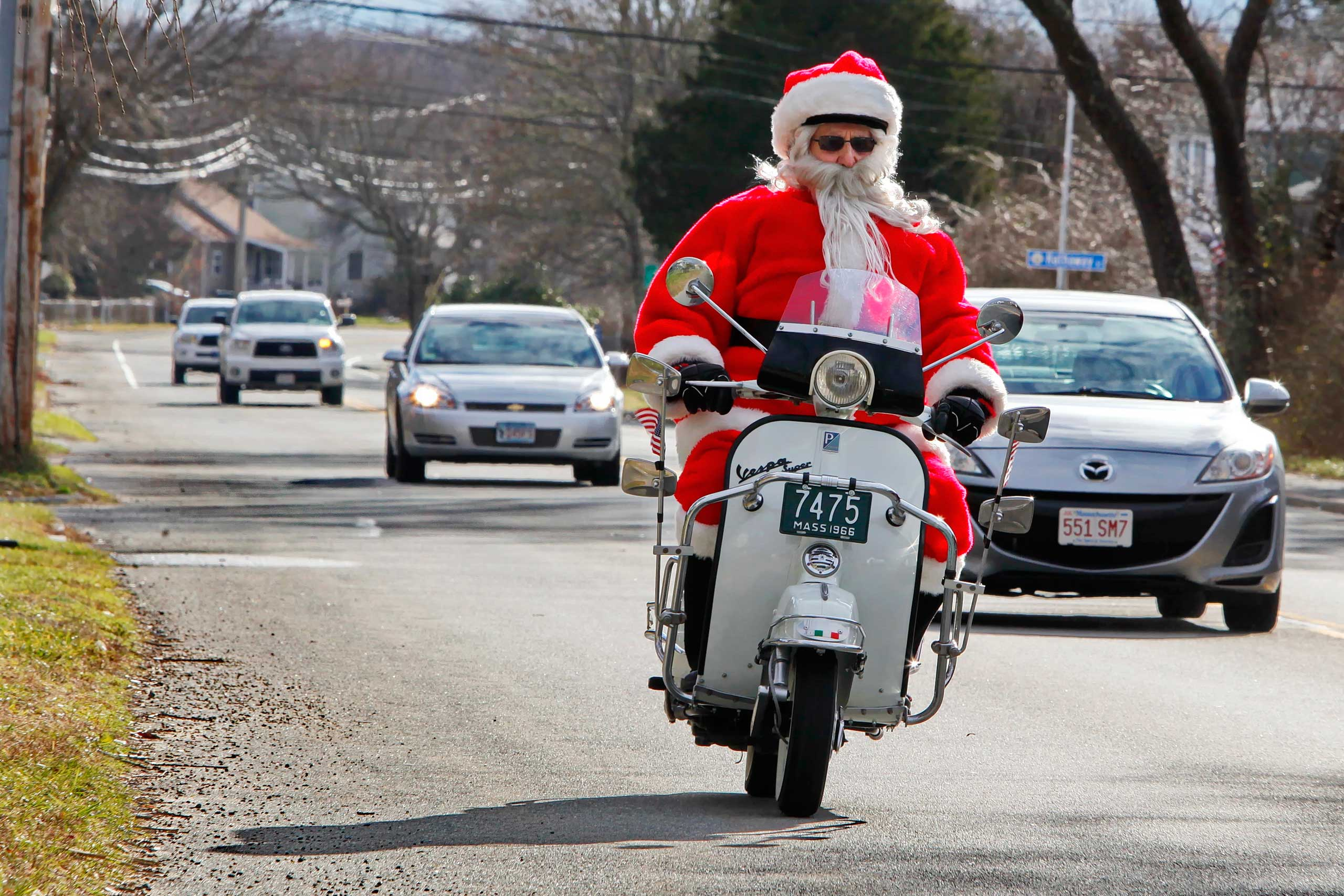 Gene Desrosiers dressed as Santa Claus rides his scooter down on Dec. 19, 2014 in Fairhaven, Mass.