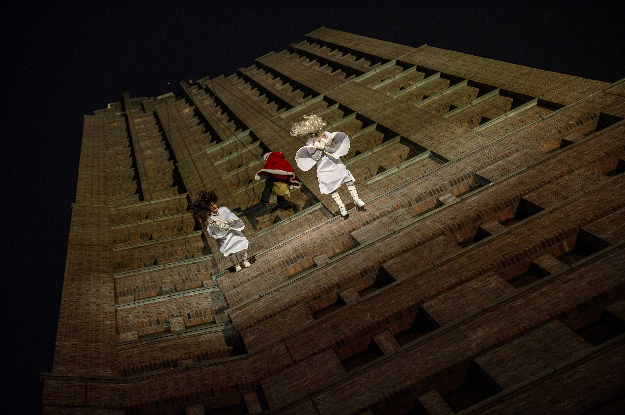 Two woman dressed as angels and Santa Claus rappel from a 100-meter high panorama point in Berlin on Dec. 14, 2014.