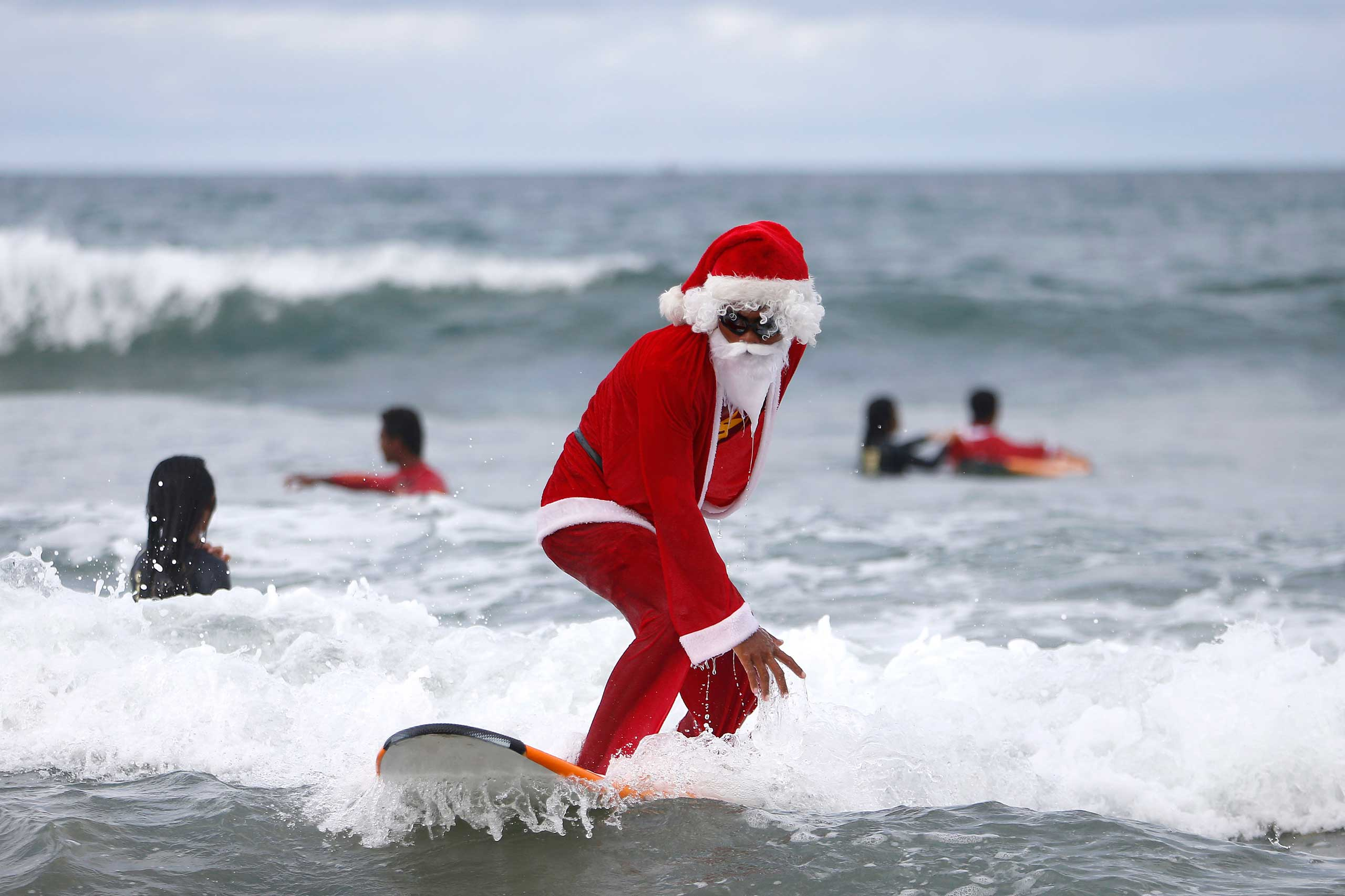 A Balinese man dressed as Santa Claus teaches orphan children how to surf at a beach in Bali, Indonesia on Dec. 7, 2014.