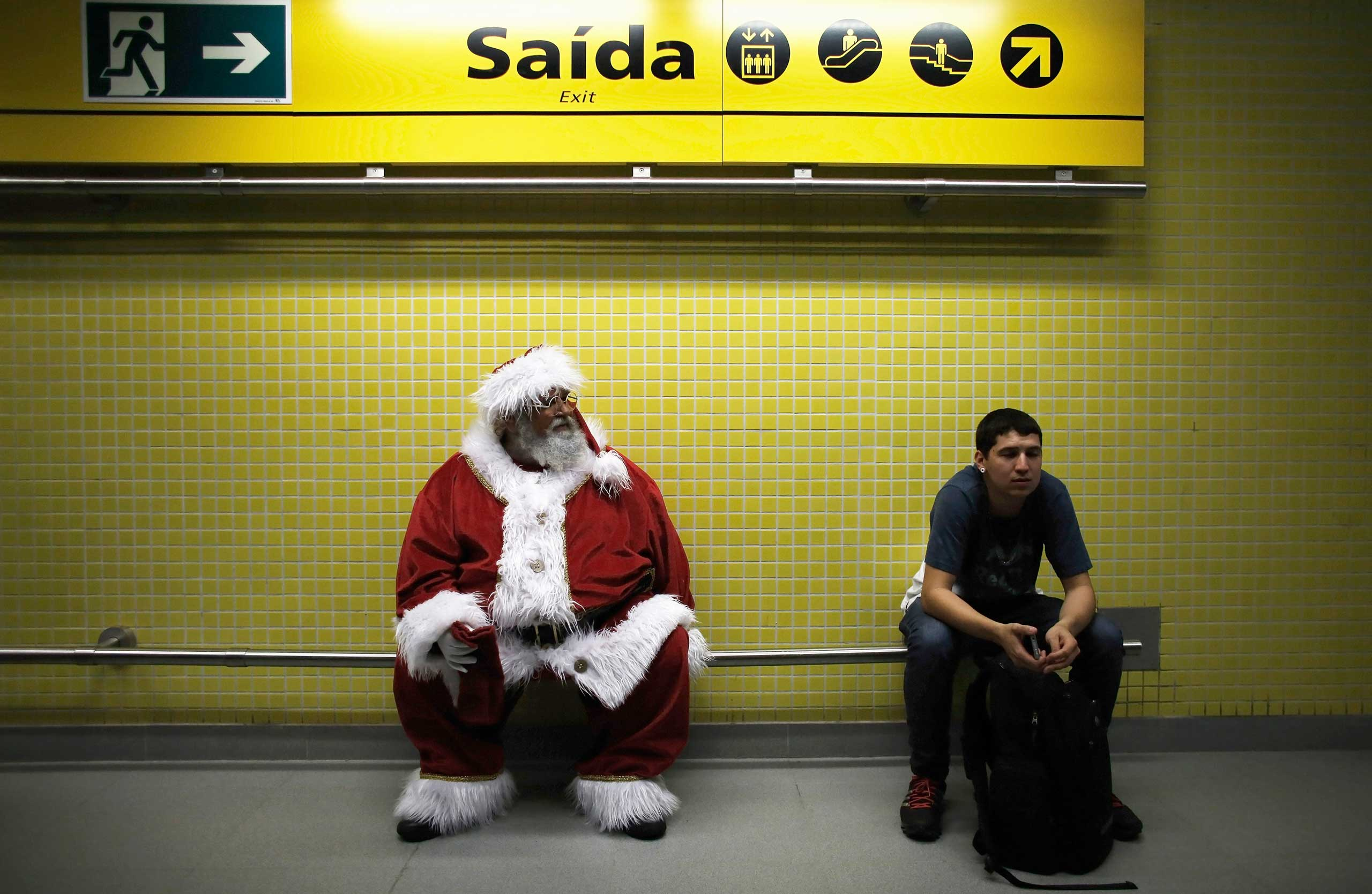 A man dressed as Santa Claus waits to board a train at a subway station in Sao Paulo on Dec. 12, 2014.