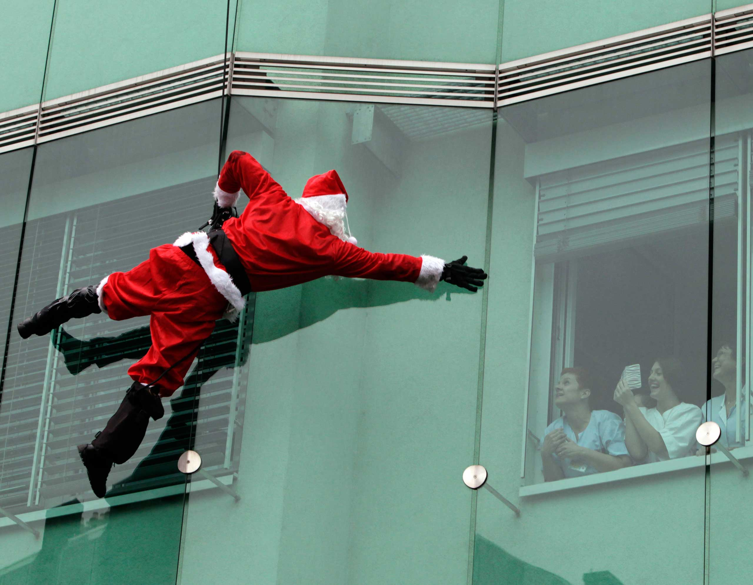 A member of the special police forces dressed as Santa Claus suit waves to staff as he descends from the roof of a pediatrics clinic in Ljubljana, SLovenia on Dec. 16, 2014.