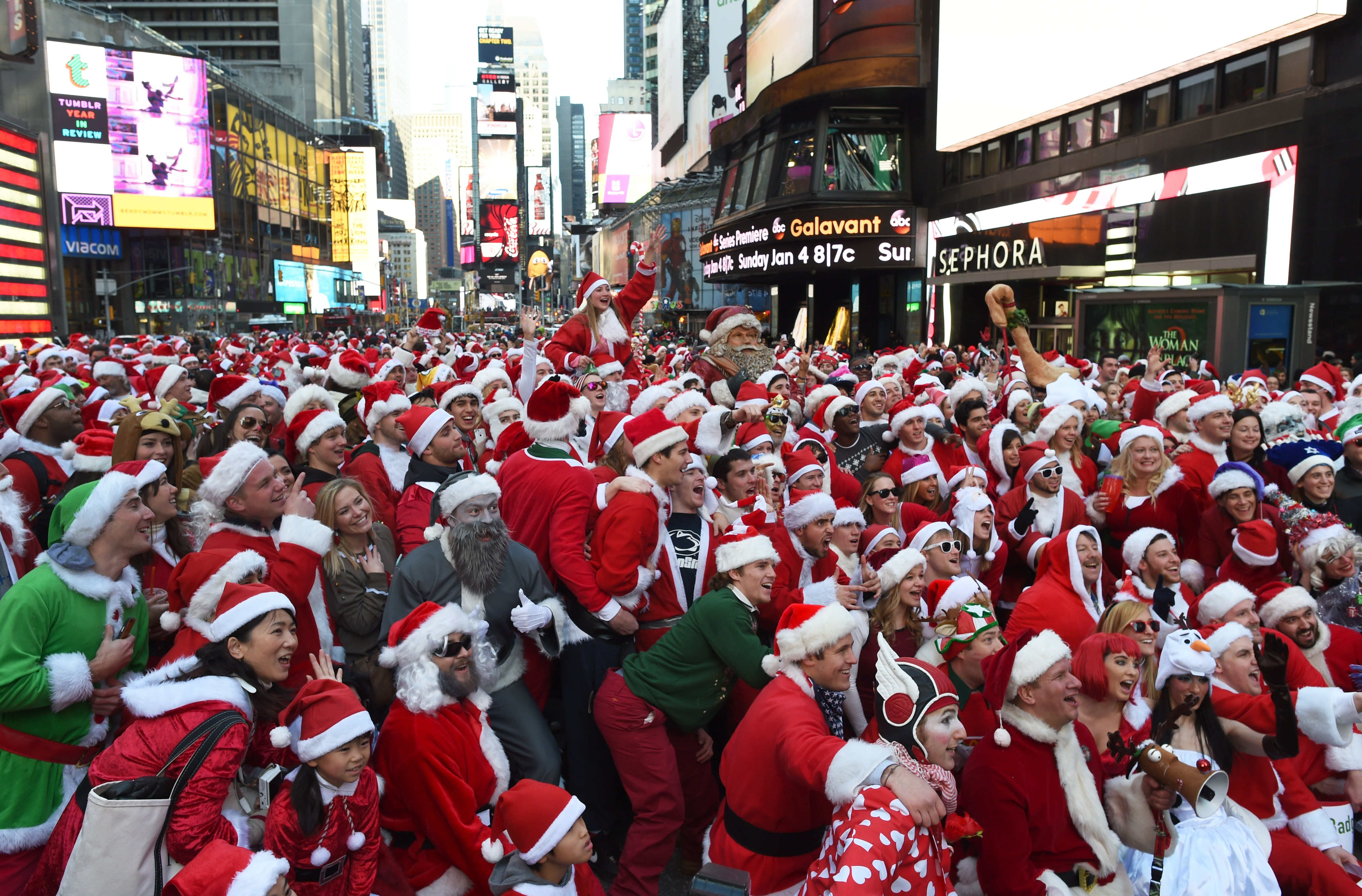 People dressed as Santa Claus and Mrs. Claus celebrate in Times Square as they gather for the annual Santacon festivities on Dec. 13, 2014 in New York.